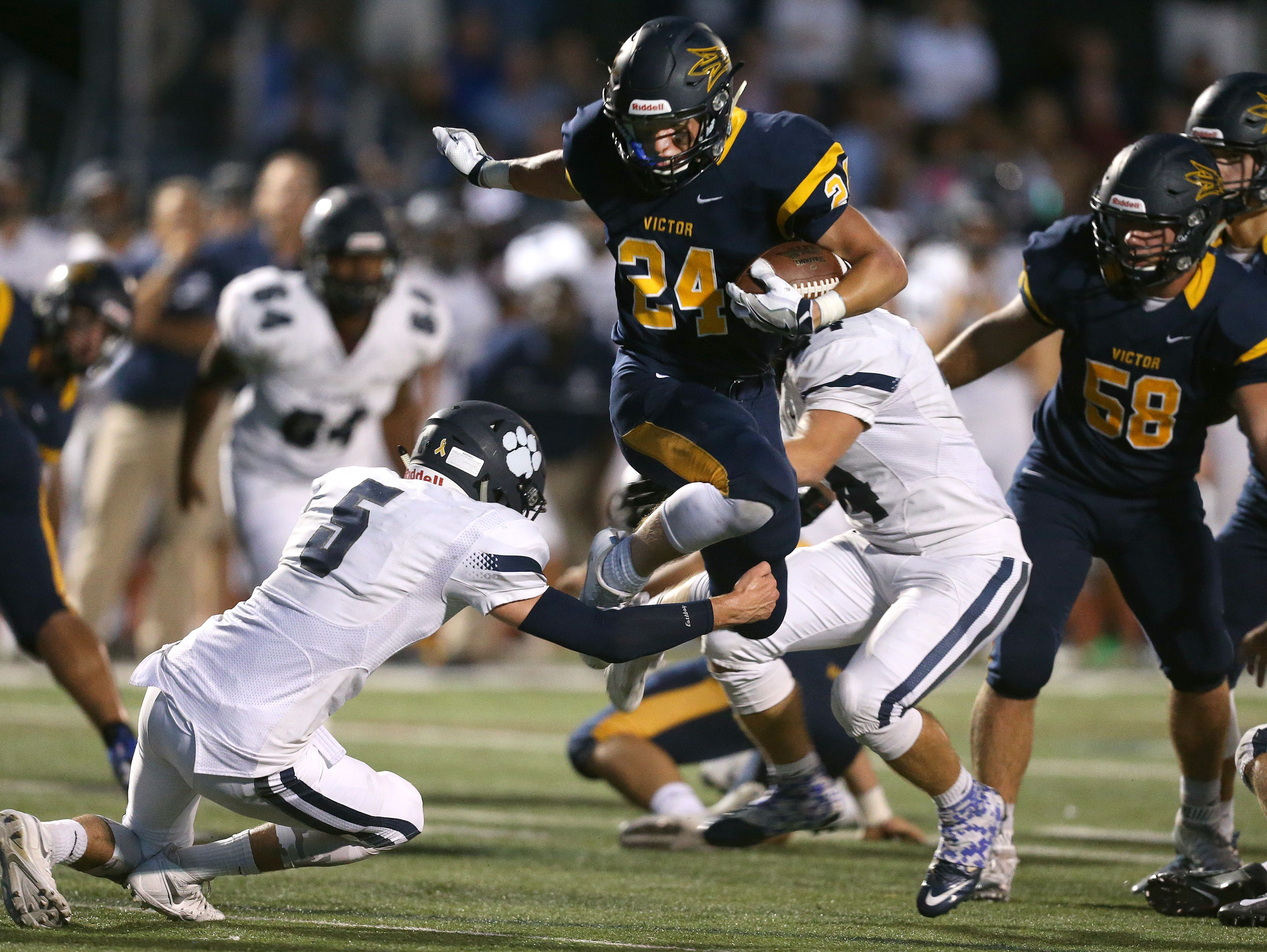 Victor running back Mitchell Spindler (24) leaps over the Pittsford's Frankie Imburgia (5).