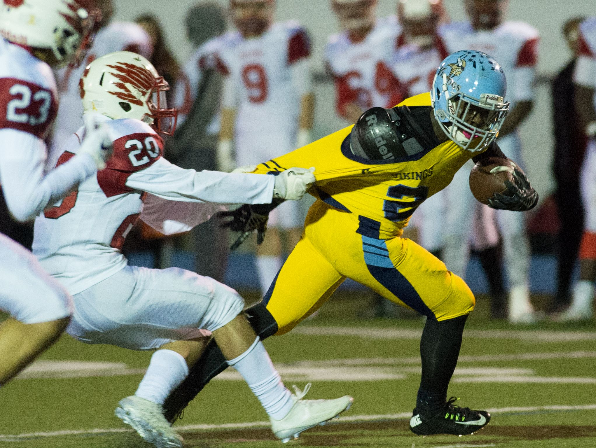 Smyrna's Jake Kaiser (20) grabs the jersey of Cape Henlopen's Rasheed Woods (2) to stop his run down the field.