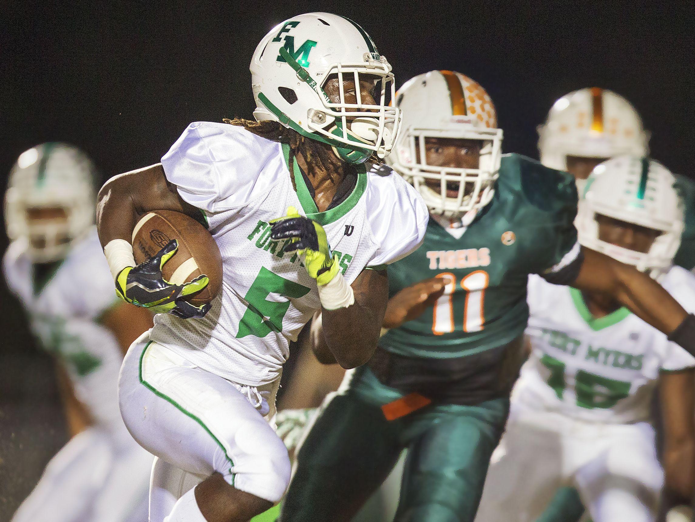 Fort Myers High School's Darrian Felix scores a touchdown against Dunbar during first quarter play Friday at Dunbar High School in Fort Myers.