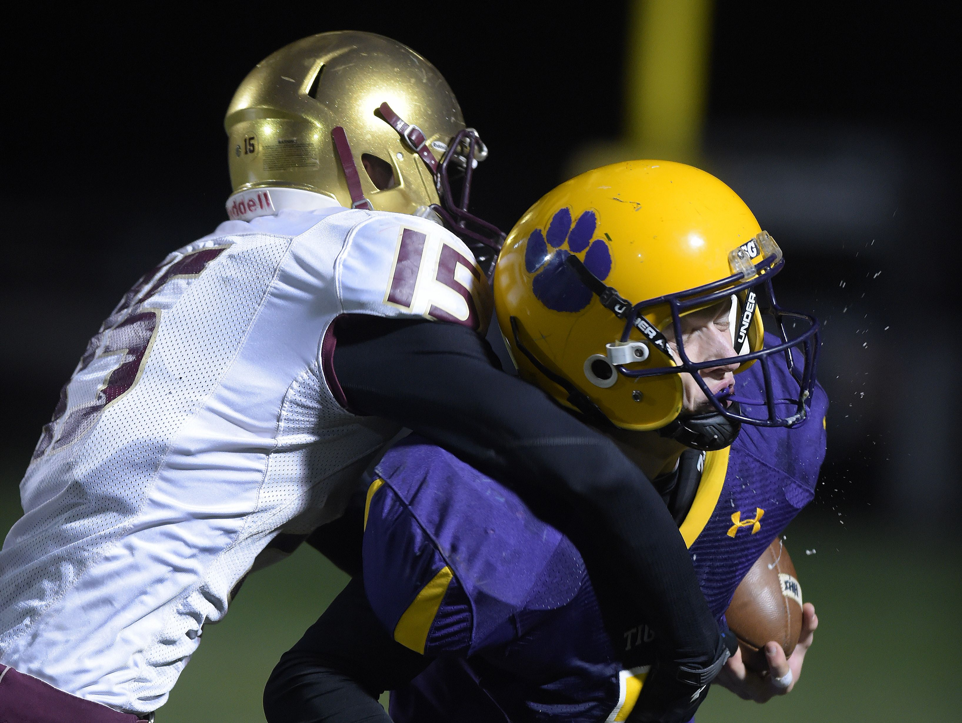 Hagerstown's Owen Golliher is hit by Indianapolis Lutheran's Austin Bryant while running the ball in a sectional football game Friday, Nov. 4, 2016 in Hagerstown.