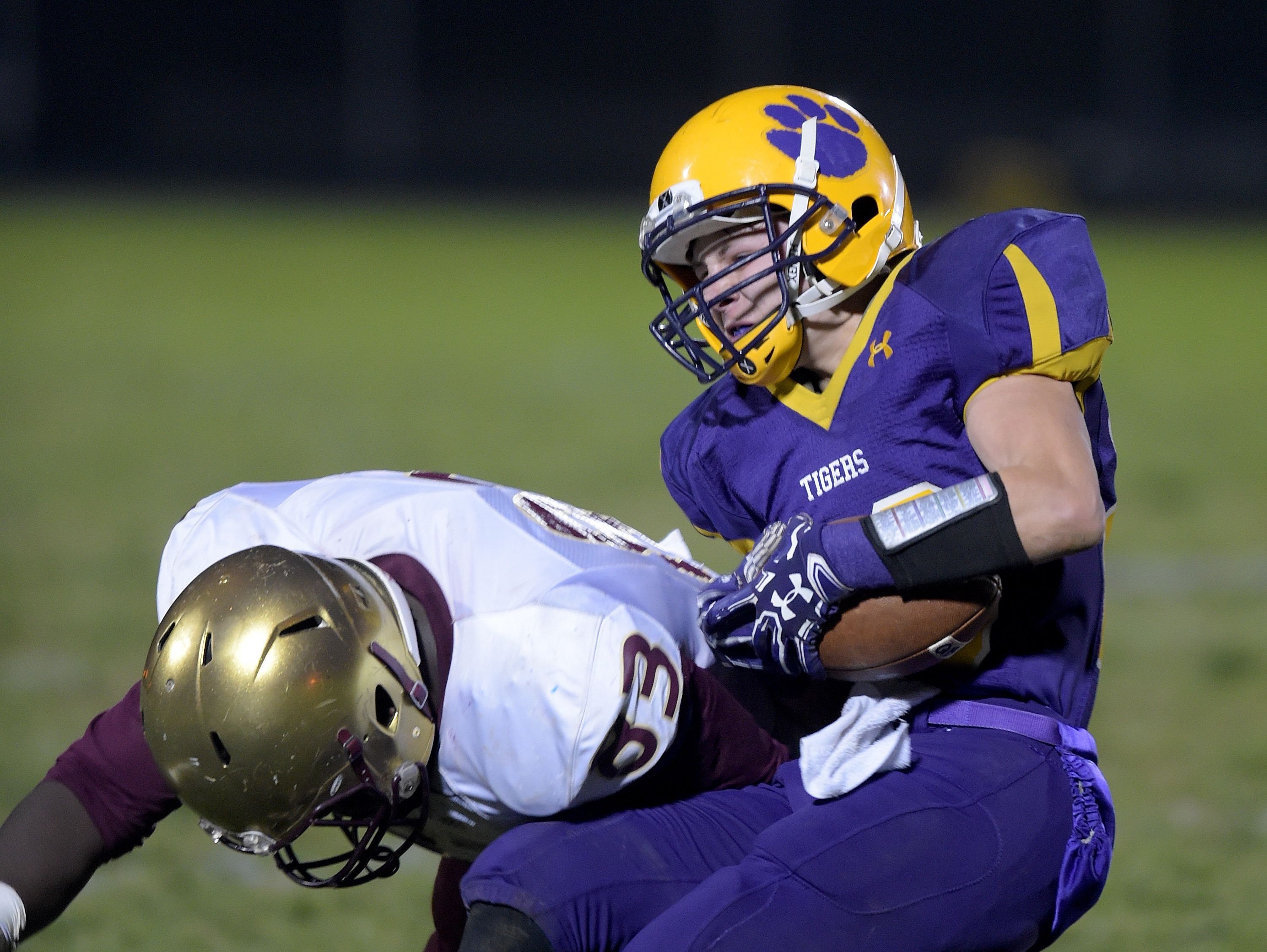 Hagerstown's Brandon Purtha runs the ball against Indianapolis Lutheran's Tyler Johnson during a sectional football game Friday, Nov. 4, 2016 in Hagerstown.
