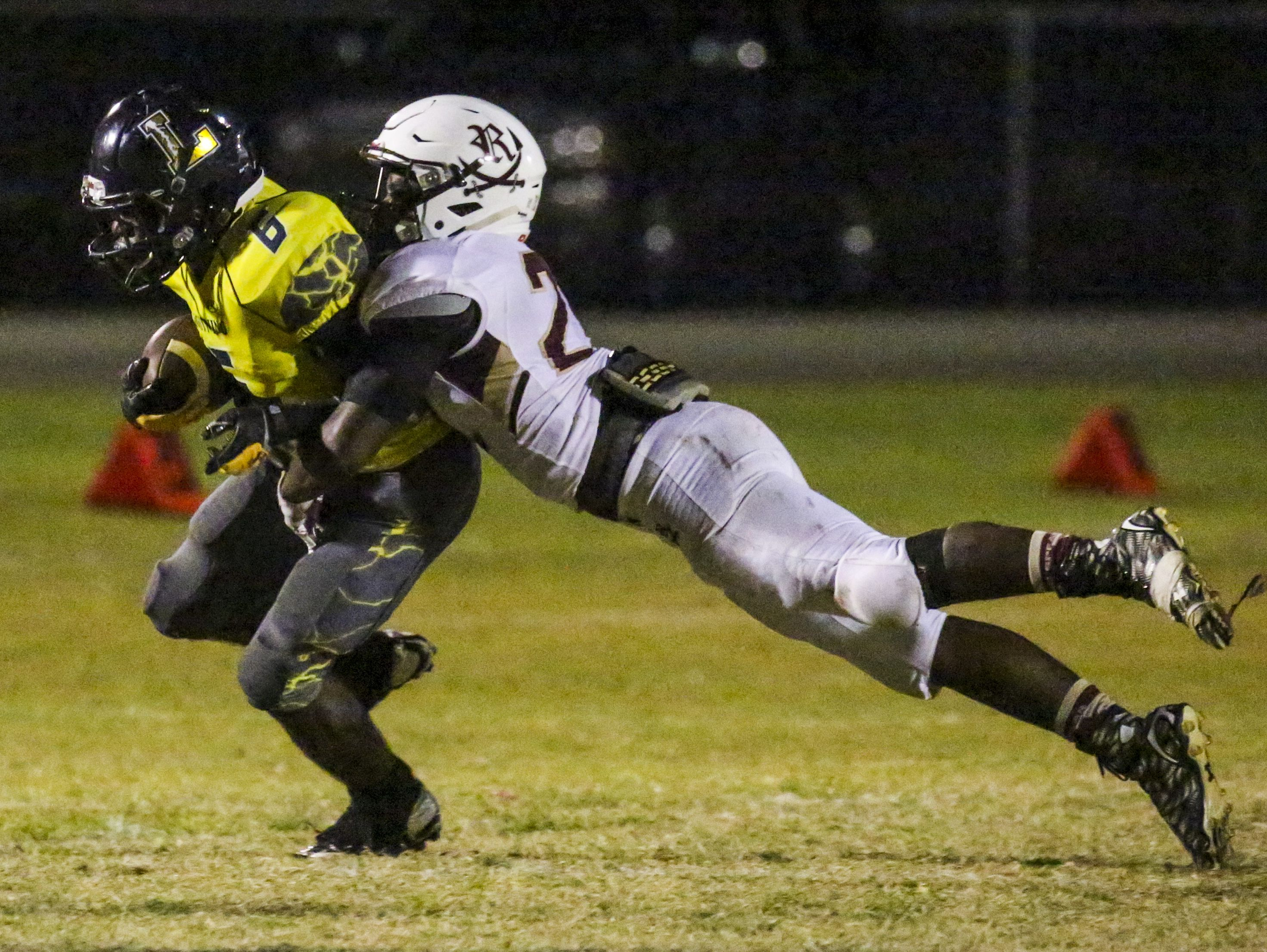 Lehigh's Jalane Nelson is brought down by Riverdale's Andres Bartley as he gains yards for the Lightning during the Riverdale at Lehigh football game.