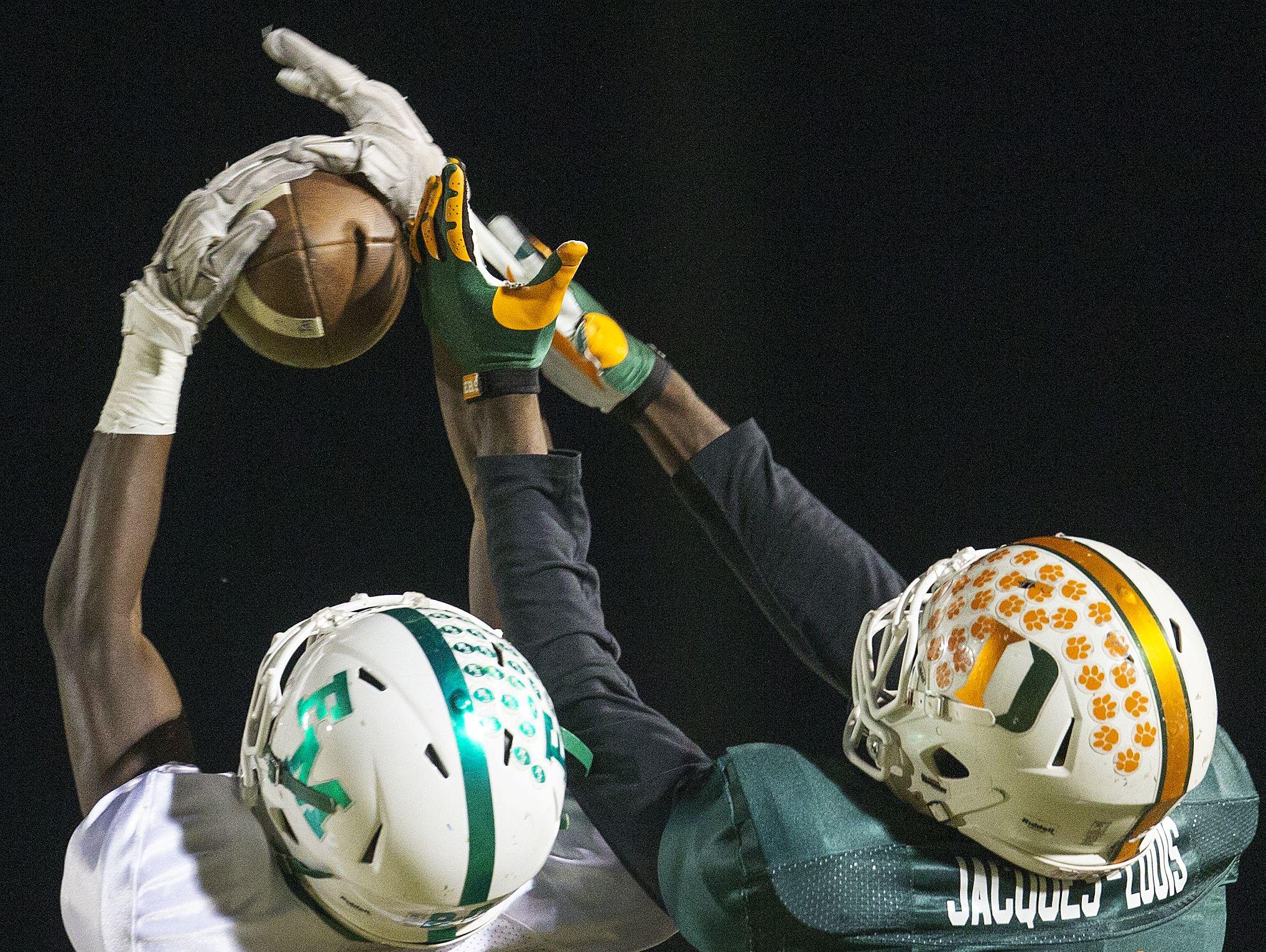 Fort Myers High School's Milan Tucker, left, intercepts a pass against Dunbar during first quarter play Friday at Dunbar High School in Fort Myers. Dunbar beat Fort Myers 29-21.