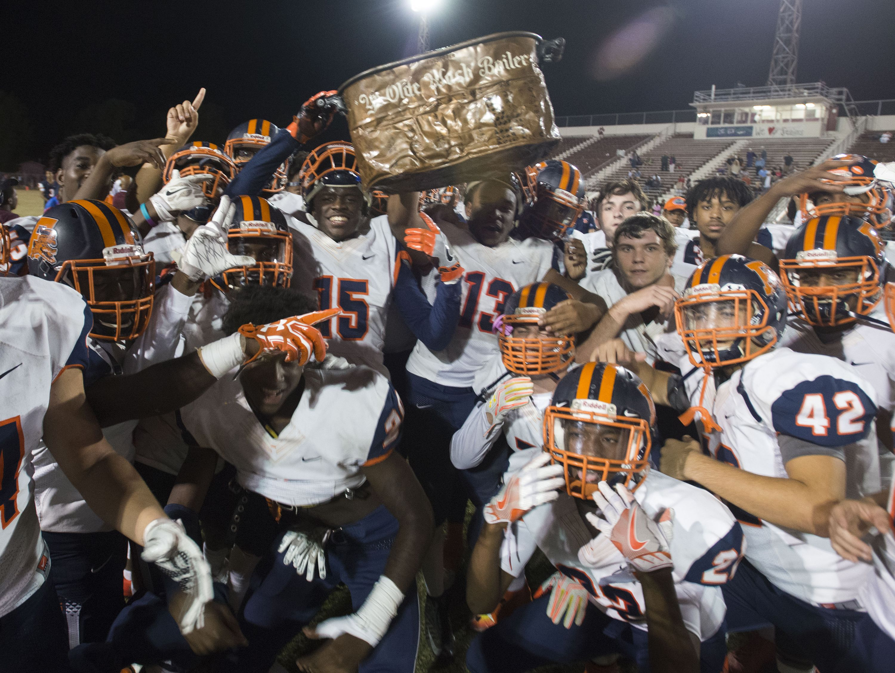 """The Escambia High School football team celebrates their victory over Pensacola High School Friday night and another year of keeping the """"Ye Olde Wash Boiler"""" prize."""