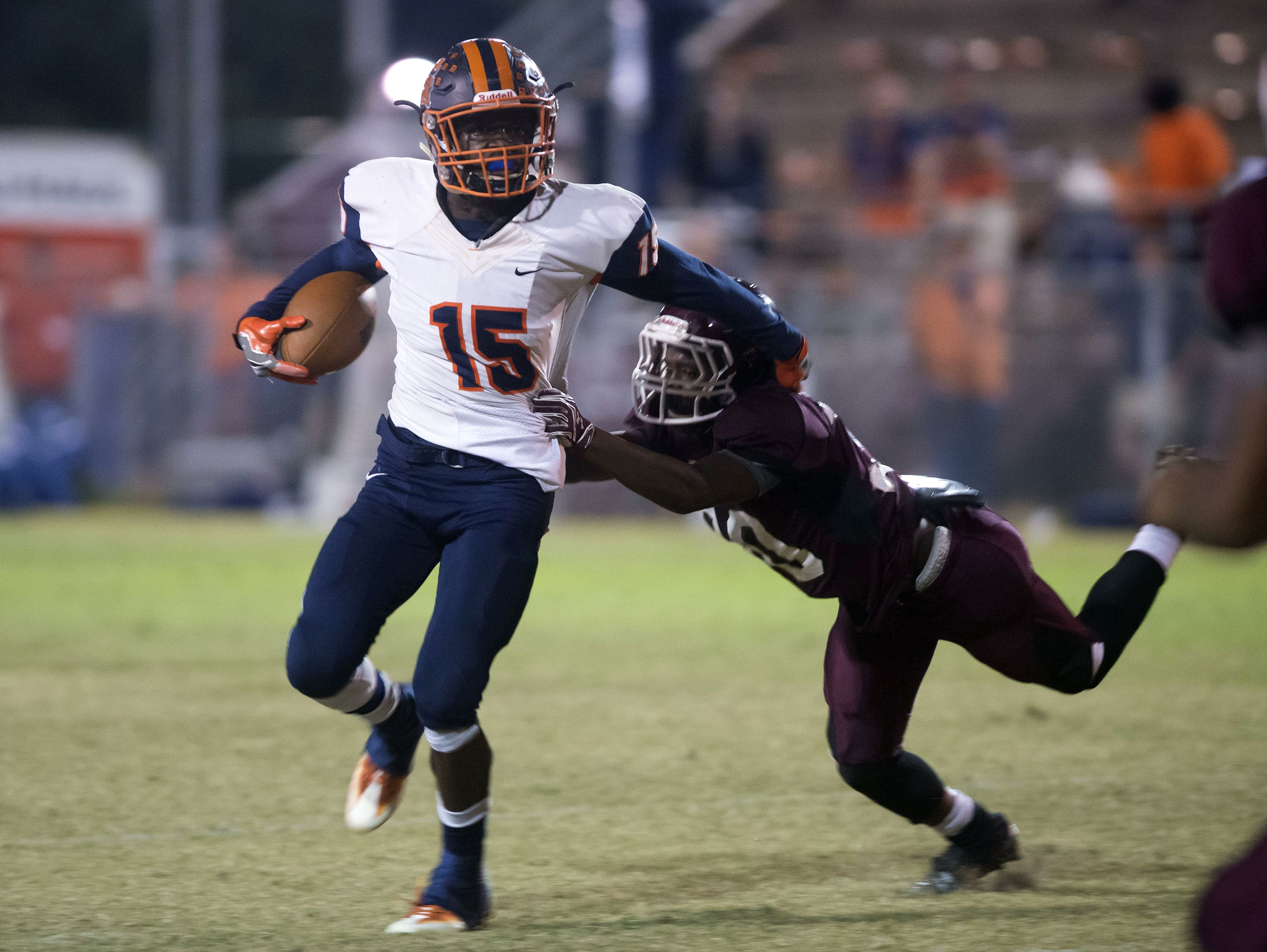 Escambia High School running back, Steven McGhee, (No. 15), shrugs off a tackle from Pensacola High School line backer, Duane Peazant, (N0. 20) during Friday night's last regular season game.