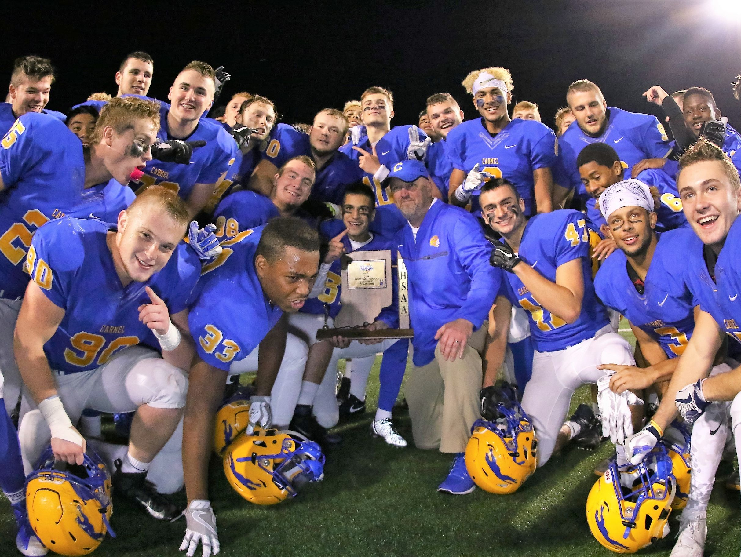 Carmel players and coaches pose with the sectional trophy after beating Fishers on Friday.