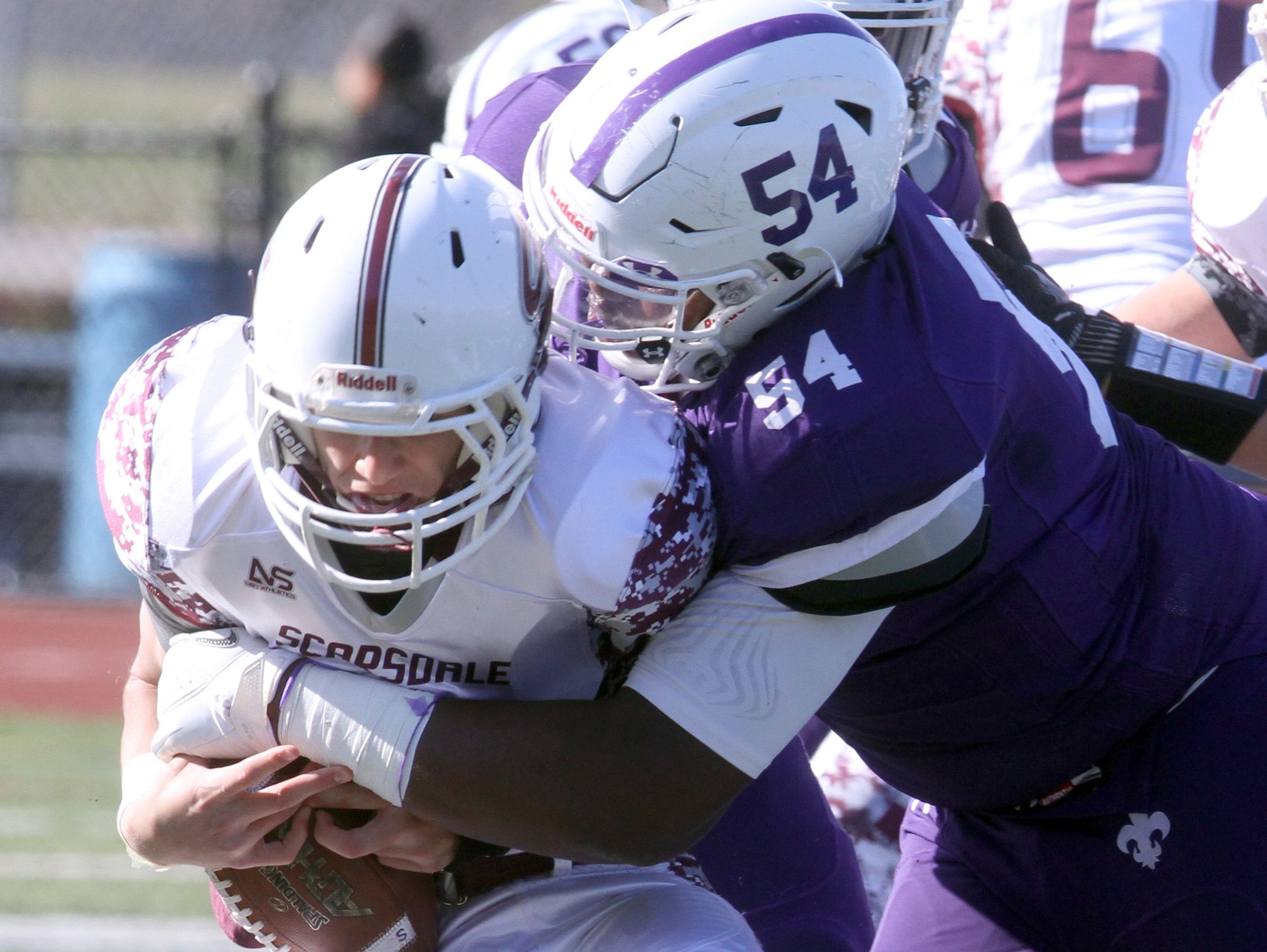 New Rochelle's Cedrice Paillant wraps up Scarsdale quarterback Barry Klein during the Section 1 Class AA football championship against Scarsdale at Mahopac High School Nov. 6, 2016. Scarsdale defeated Scarsdale 41-13 in