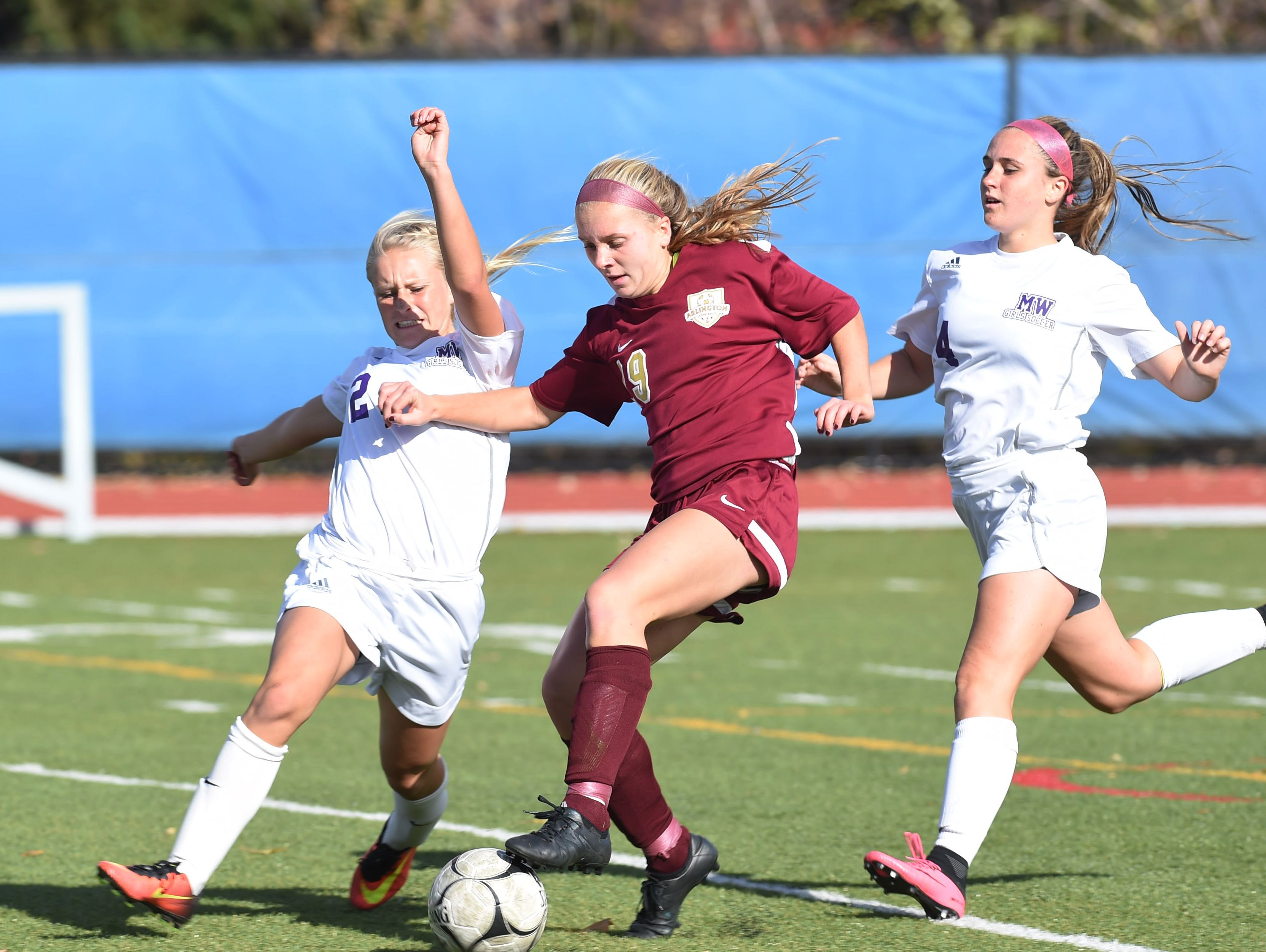 Arlington's Molly Feighan, center, tries to keep the ball away from Monroe-Woodbury's Kayla MacKenzie, left, during Saturday's Class AA regional final.