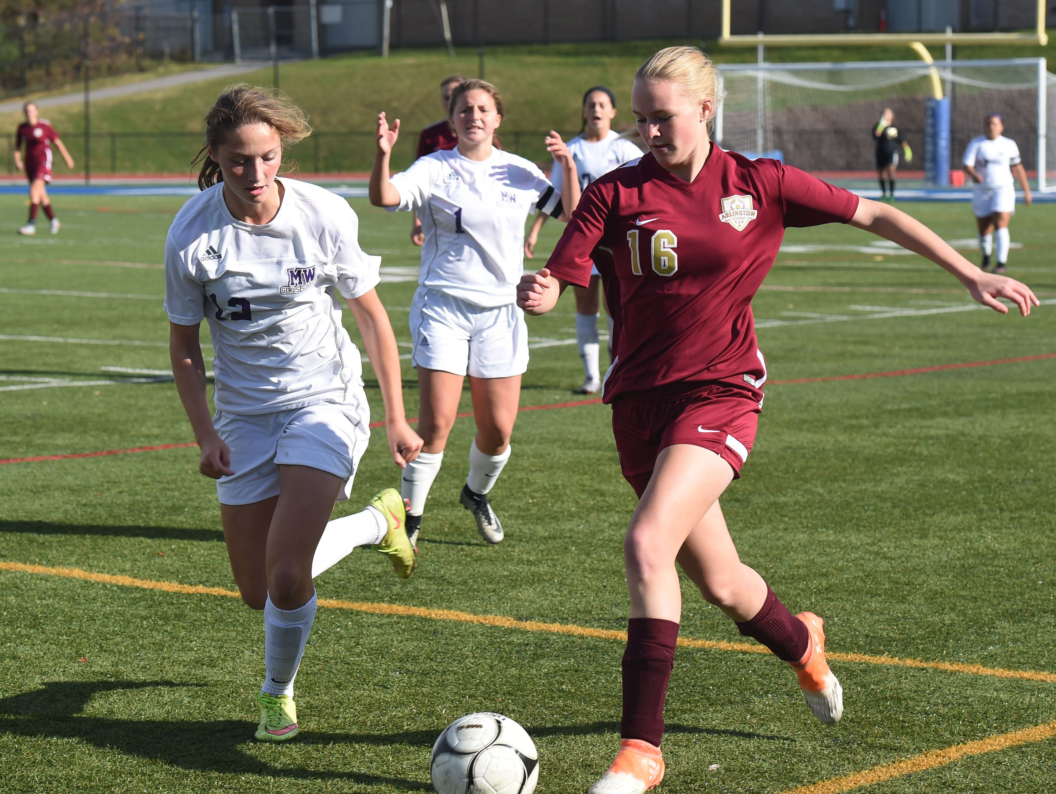 Arlington's Alexa Peruffo, right, takes the ball down the field as Monroe-Woodbury's Sydney Harwood, left, defends during Saturday's Class AA regional final.