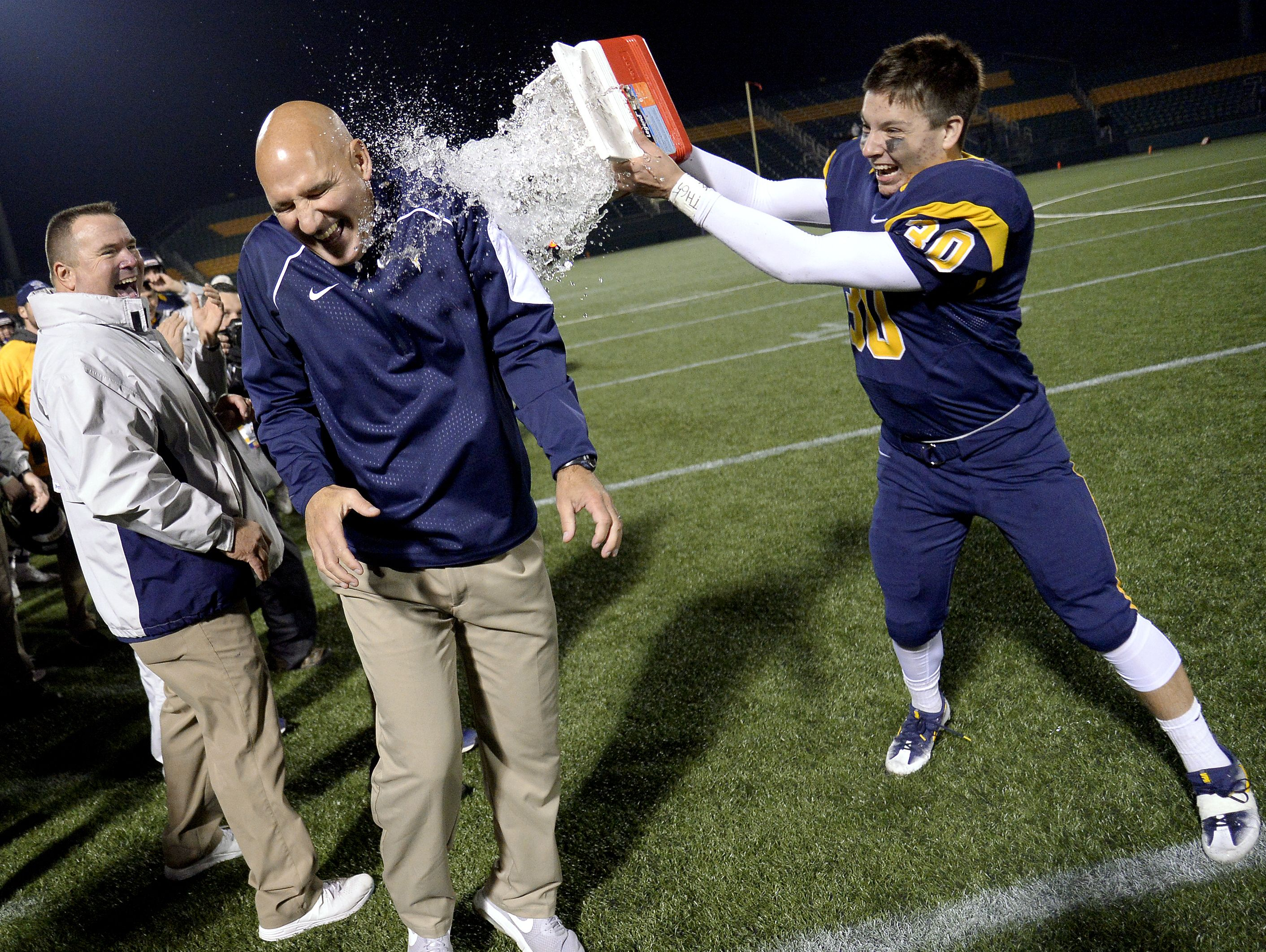 Victor head coach Geoff Mandile, left, gets doused with water by James Caggiano during the Section V Class AA final at Rhinos Stadium on Nov. 5, 2016. No. 1 seed Victor won the Class AA title with a 23-7 win over No. 2 seed Pittsford.