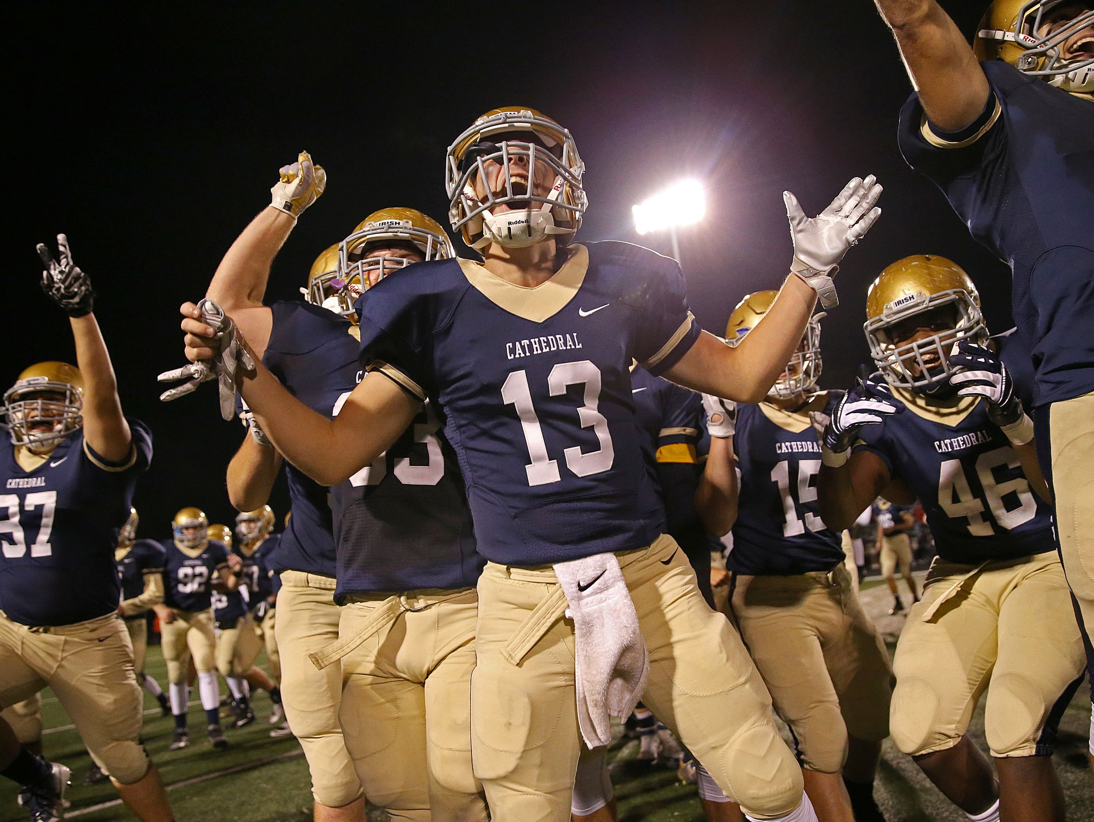 The Cathedral Fighting Irish celebrate after winning sectional finals against Lawrence Central in overtime, 20-17, at Arsenal Technical High School, Friday, November 4, 2016.