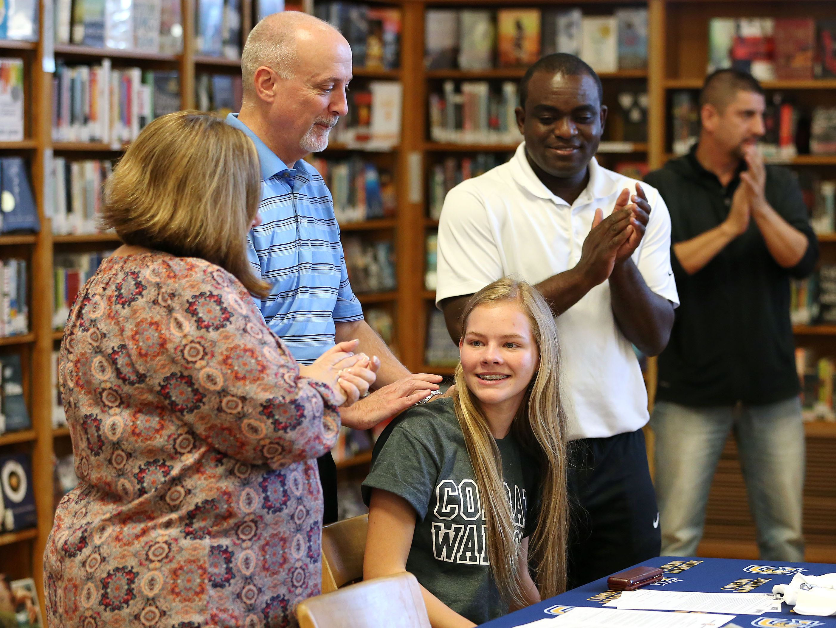 South Salem senior Hannah Hersh is surrounded by her parents, Ted and Dana Hersh, and Likius Hafemi, Corban University women's soccer head coach, as she signs a letter of intent to play soccer at Corban during a signing ceremony on Tuesday, Nov. 8, 2016, at South Salem High School.