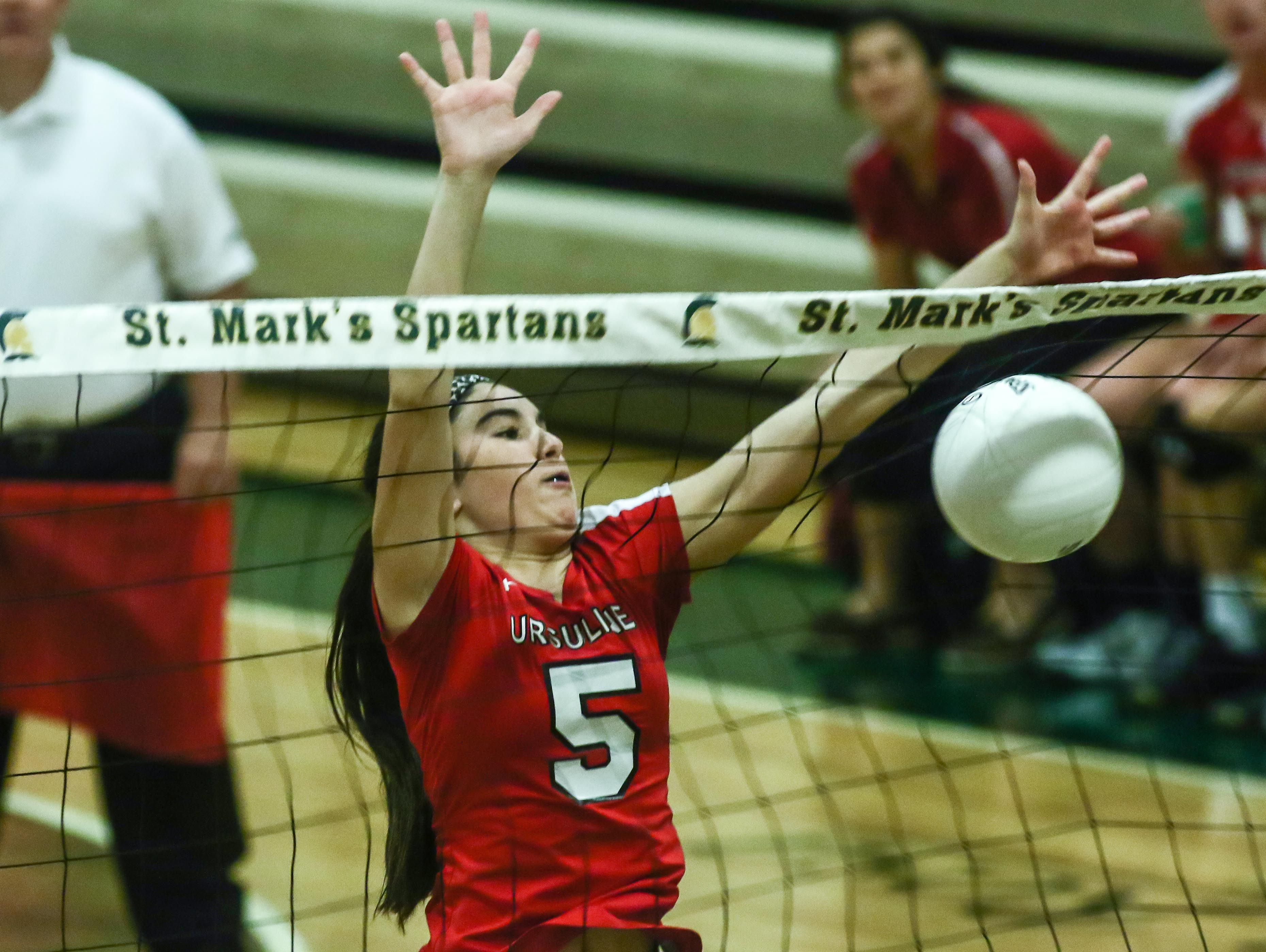 Ursuline's Kylie Nocket (5) jump up to block a spike during a DIAA Girls Volleyball quarterfinals match between Padua and Ursuline on Tuesday at St. Mark's High School in Wilmington.