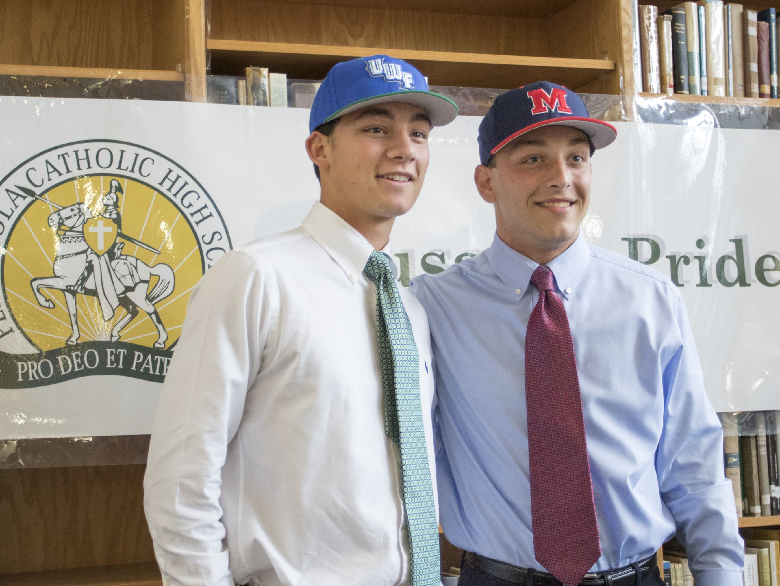 Athletes Matthew Estrada (University of West Florida), left, and Carl Gindl (University of Mississippi) sport hats after signing letters of intent to play baseball for their respective colleges during a press conference at Catholic High School in Pensacola on Wednesday, November 9, 2016.