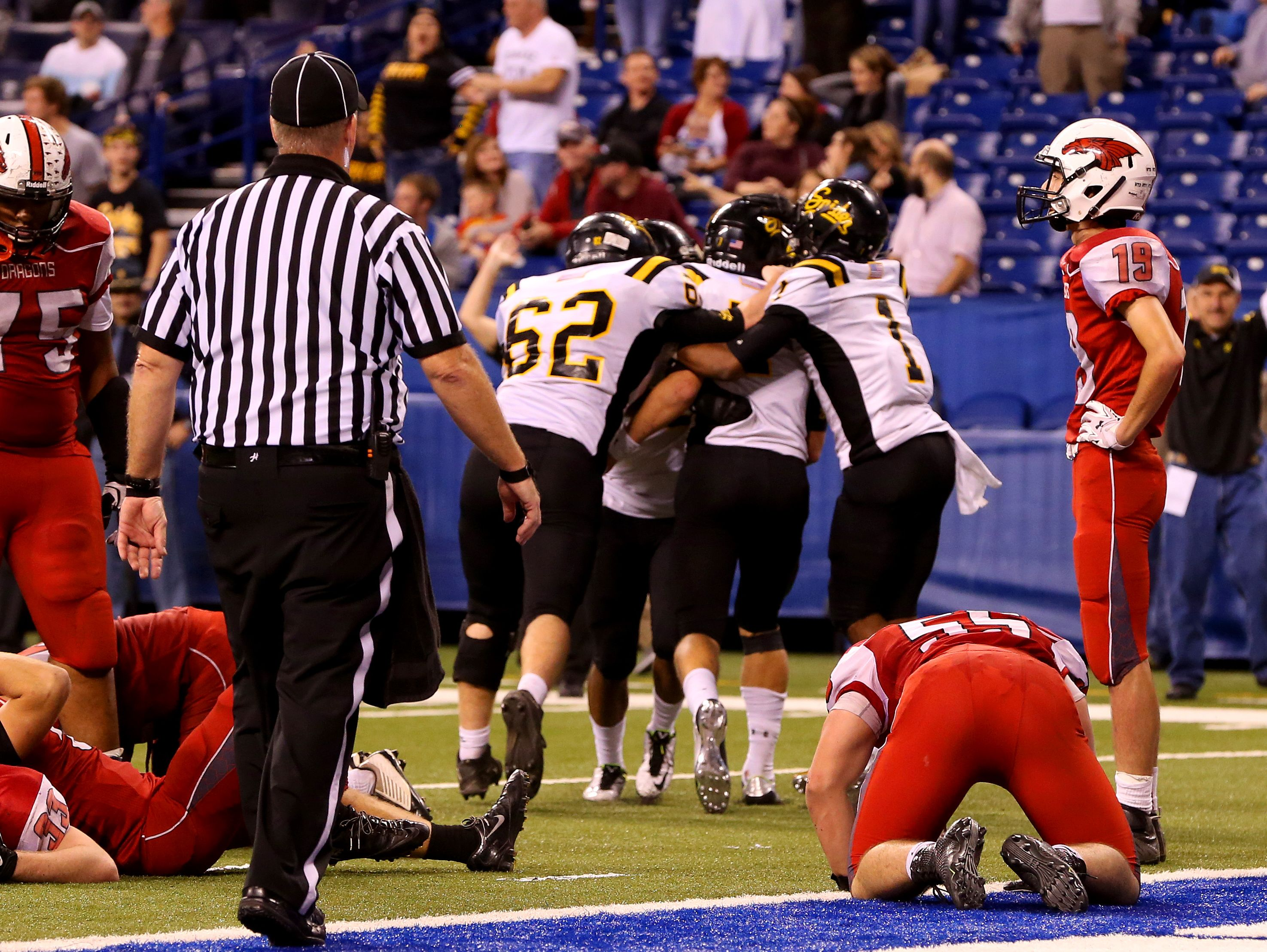 New Palestine Dragons show their disappointment after allowing a last minute Fort Wayne Snider touchdown in the Class 5A IHSAA Football State Tournament finals at Lucas Oil Stadium on Nov. 27, 2015.