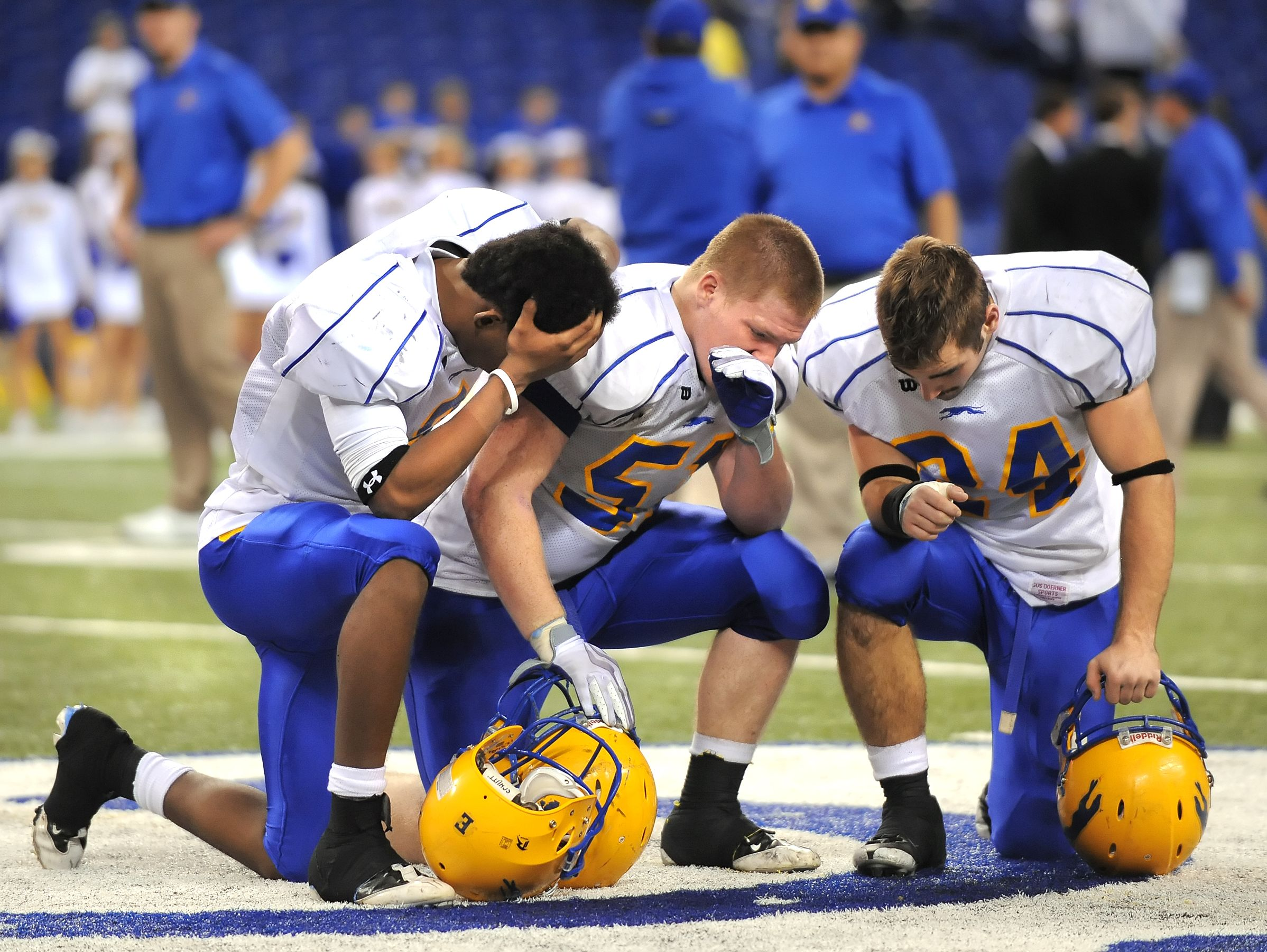 FILE – Carmel players (from left) Chase Varndell, John Wood and Ronnie Fowlkes feel the double overtime loss to Warren Central in the 5A state finals at Lucas Oil Stadium on Nov. 28, 2009.