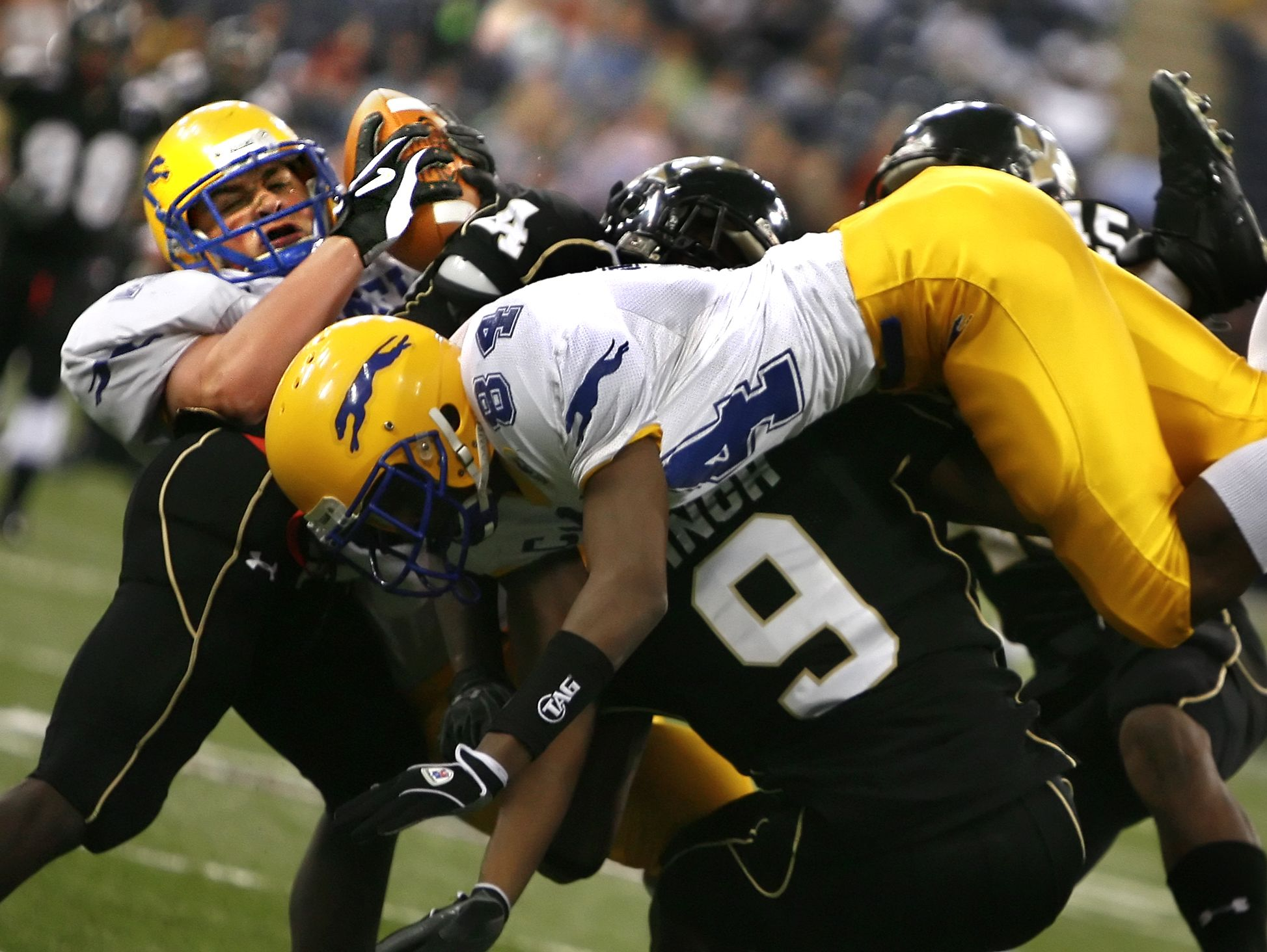 FILE – Carmel tight end Ryan Murray (back left w/ball) comes down with a pass that was intended for teammate Jordan Brewer (foreground) despite tight defense from Warren Central in the Class 5A State Finals held at the RCA Dome.