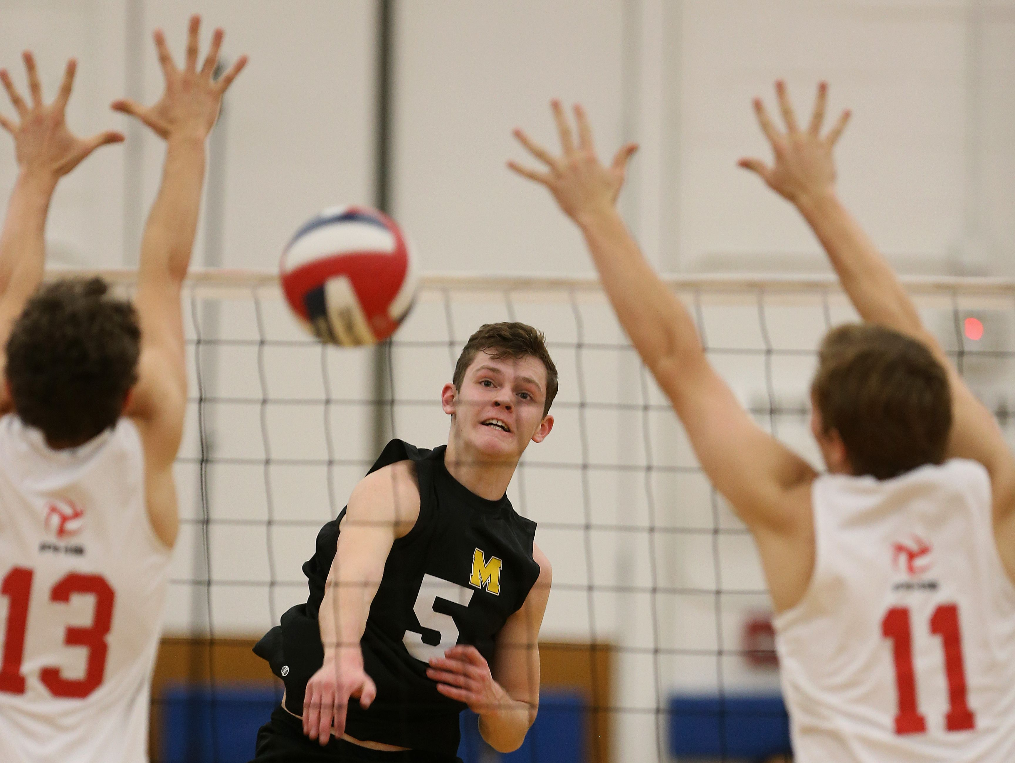 McQuaid's Spencer Wickens goes up for the kill against Penfield's Andy Scott (13) and Jack Burke.