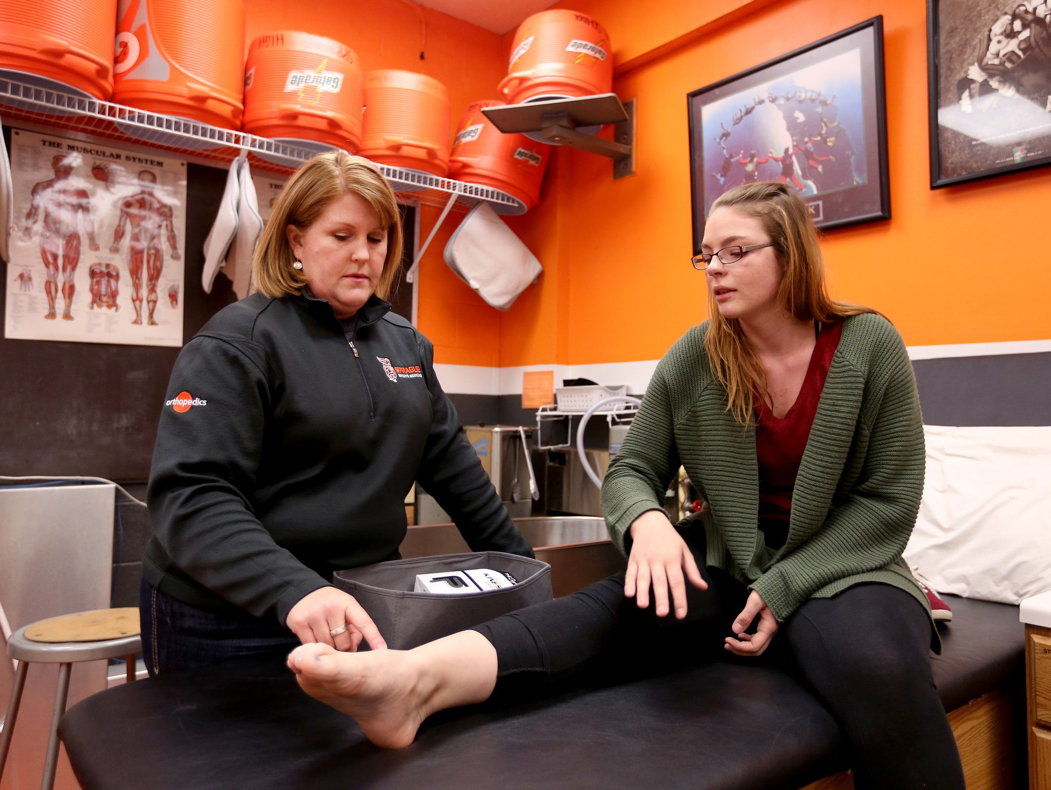 Athletic Trainer Amy West, left, helps junior Kaylyn Morgan with an ankle and foot injury from a car accident at Sprague High School in Salem on Tuesday, April 5, 2016.