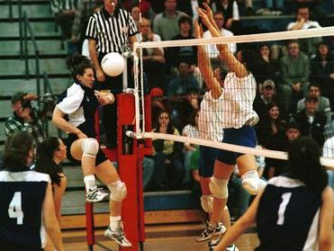 Waynesboro's Katie Steidle (left) has an attack blocked by Lee's Celena Gray, and Whitney Vaughn during the 1999 season. Vaughn is now an assistant coach for Lee volleyball.