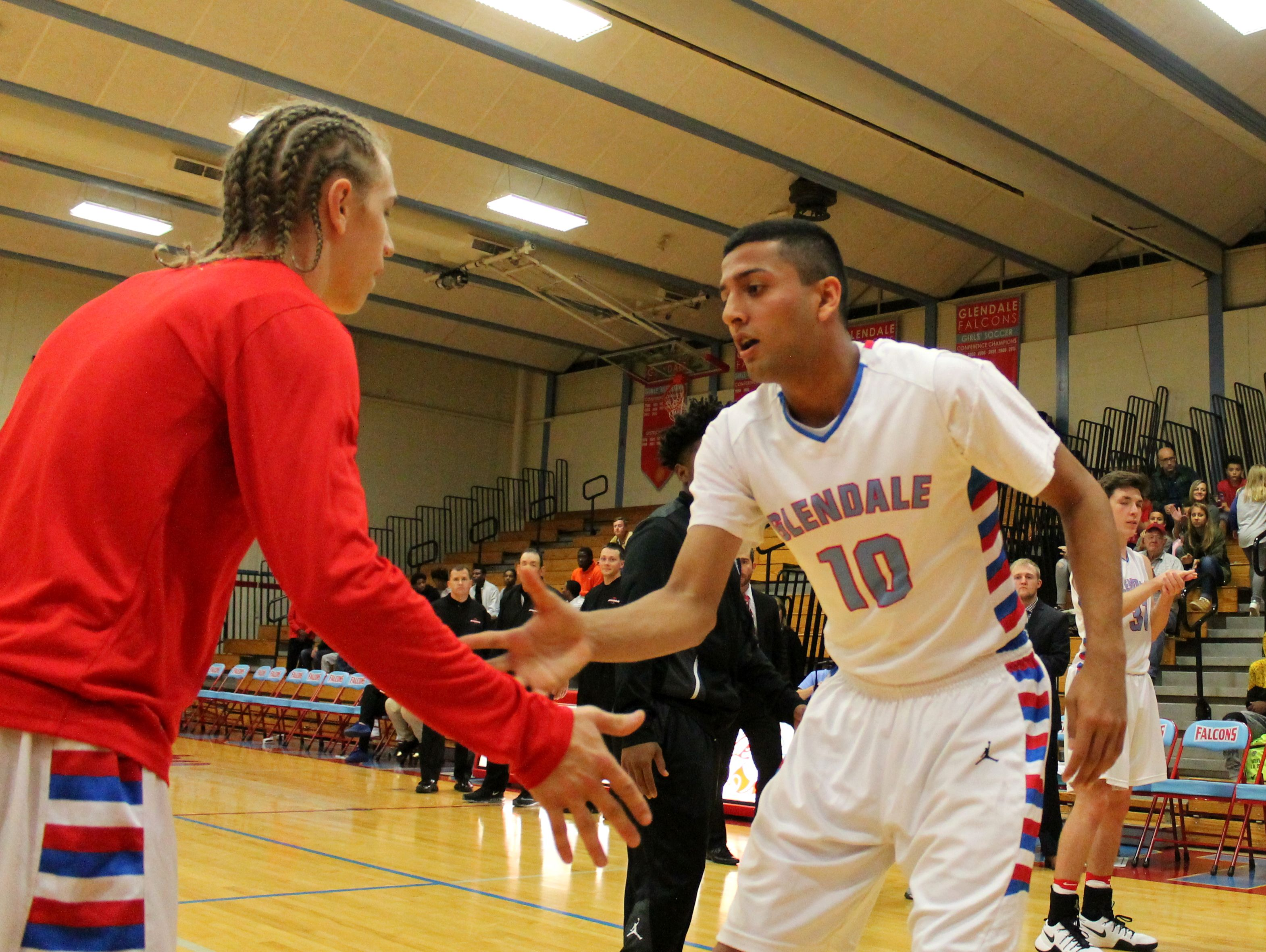 Glendale junior Monty Johal (right) low fives teammate Von Oeser (left) before Glendale's 2015-2016 season-opening home win over Carnahan.