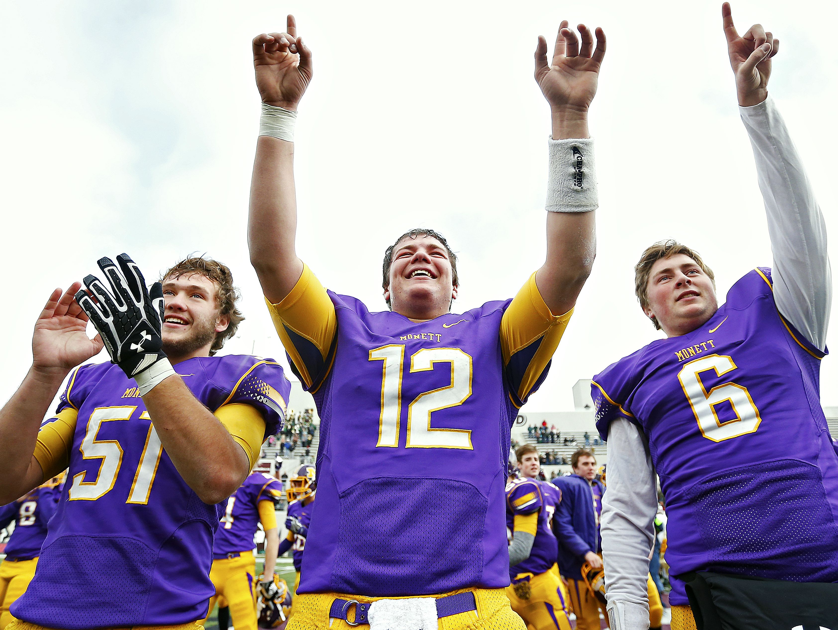 Monett High School center Caleb Hilton (51) and quarterbacks Ian Meyer (12) and Tommy Sangston (6) celebrate after the end of the MSHSAA Class 3 State Championship Game between the Monett High School Cubs and the Maryville High School Spoofhounds at Robert W. Plaster Stadium in Springfield, Mo. on Nov. 26, 2016. The Monett Cubs won the game 27-18.