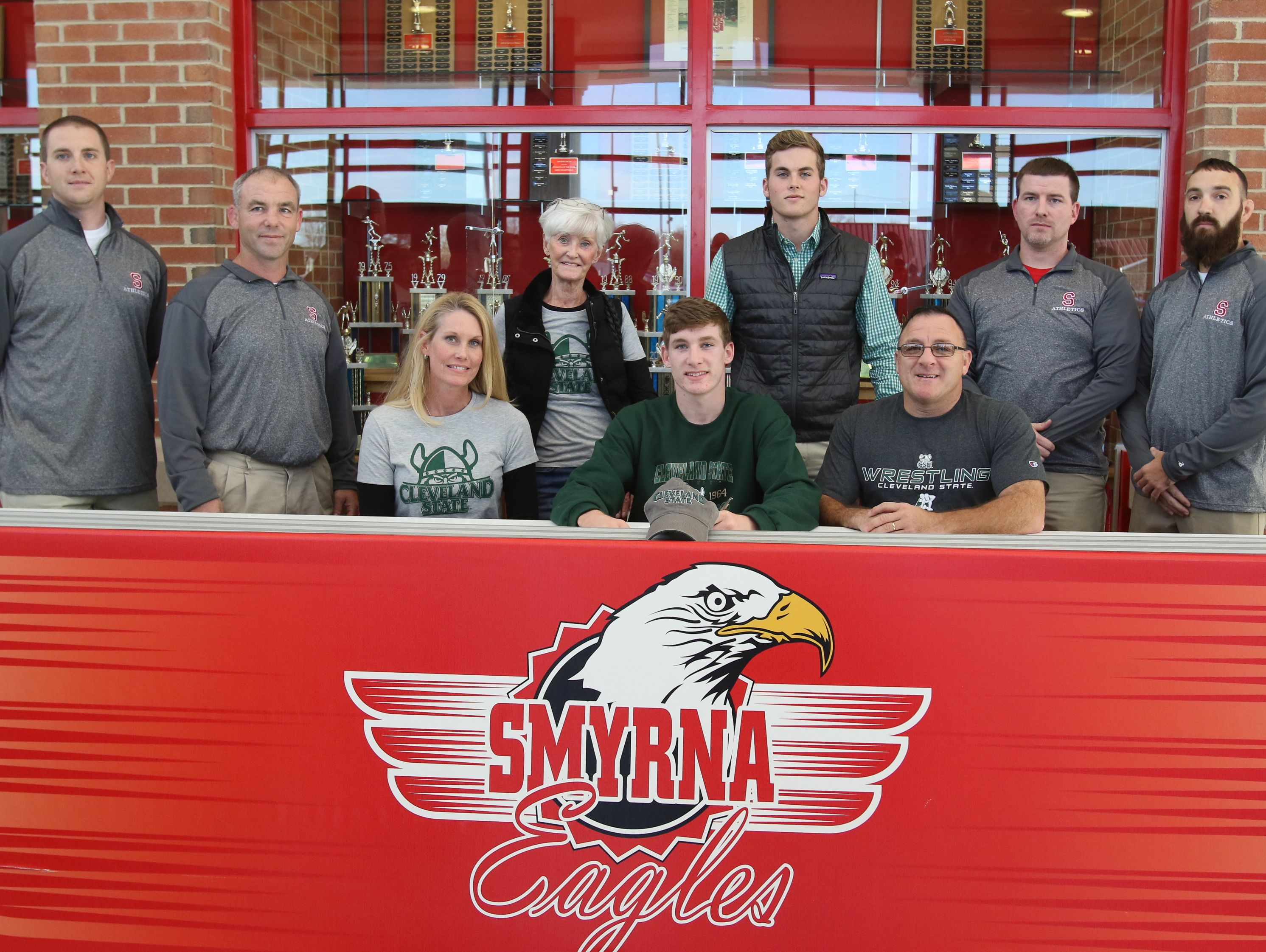 Smyrna wrestler Chase Archangelo is surrounded by his family and coaches while signing a National Letter of Intent with Cleveland State.