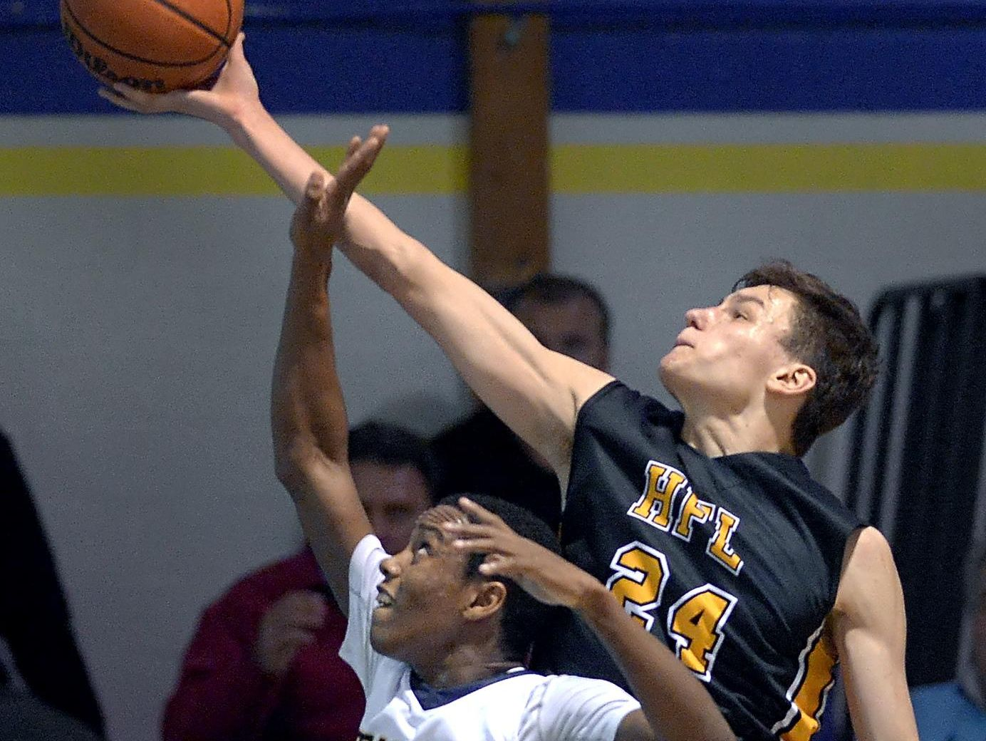 Honeoye Falls-Lima's Tommy Eastman, right, reaches over Brighton's Alex Jordan for a rebound during a regular season game played at Brighton High School on Wednesday, Feb. 3, 2016. HF-L beat Brighton 54-43.