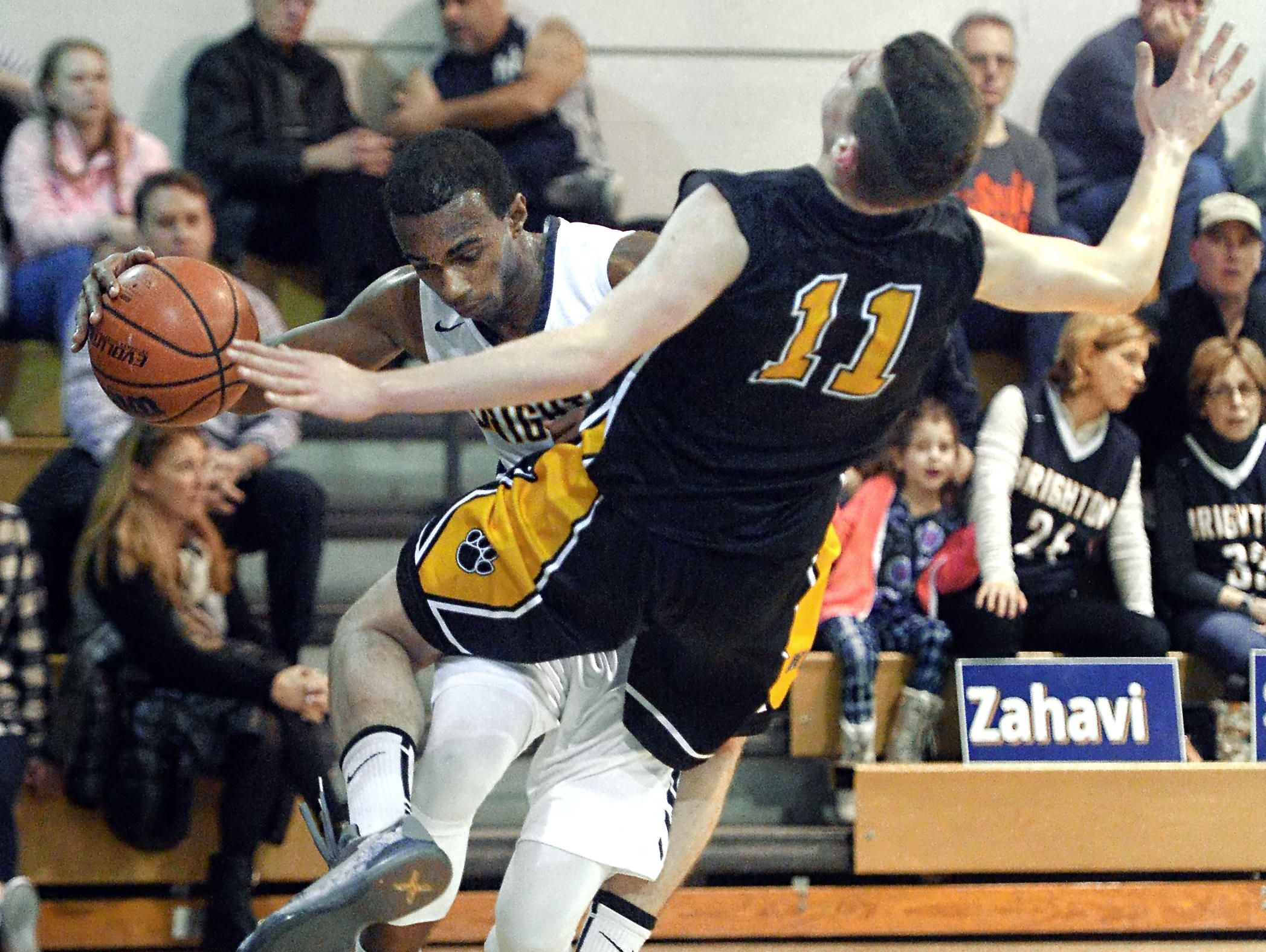 Honeoye Falls-Lima's Josh D'Agostino, right, draws a charge on Brighton's Miles Davis during a game played at Brighton High School on Wednesday, Feb. 3, 2016.