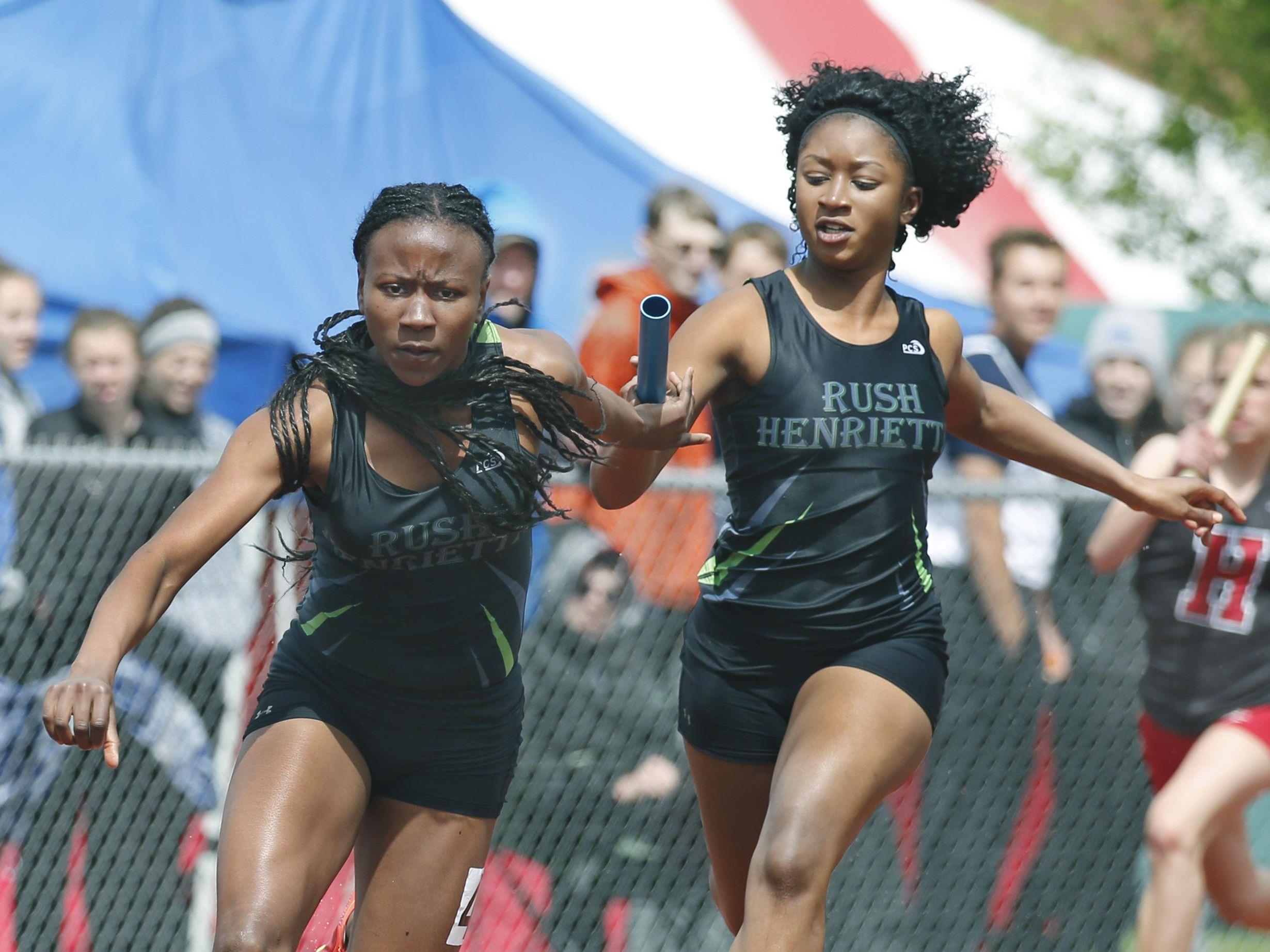 Rush-Henrietta's Lanae-Tava Thomas takes the baton from Adama Donzo to win the 4 x 100 meter relay during the Royal Comet Invitational at Rush-Henrietta High School.