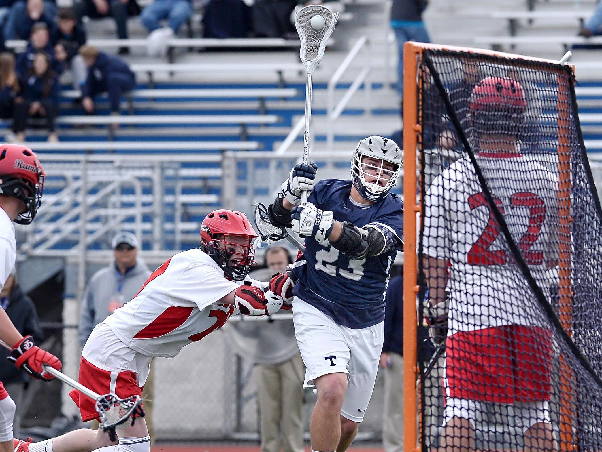 Webster Thomas' Pierce Currie, center, shoots at the Jamesville-Dewitt goal.