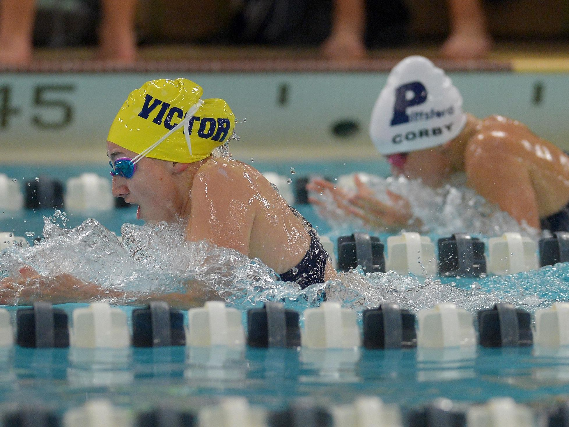 Victor's Mia Baggett, left, leads Pittsford's Emma Corby to win the 100 yard breaststroke with a time of 1:10.11 during regular season meet at Pittsford Mendon High School on Thursday, Sept. 8, 2016.