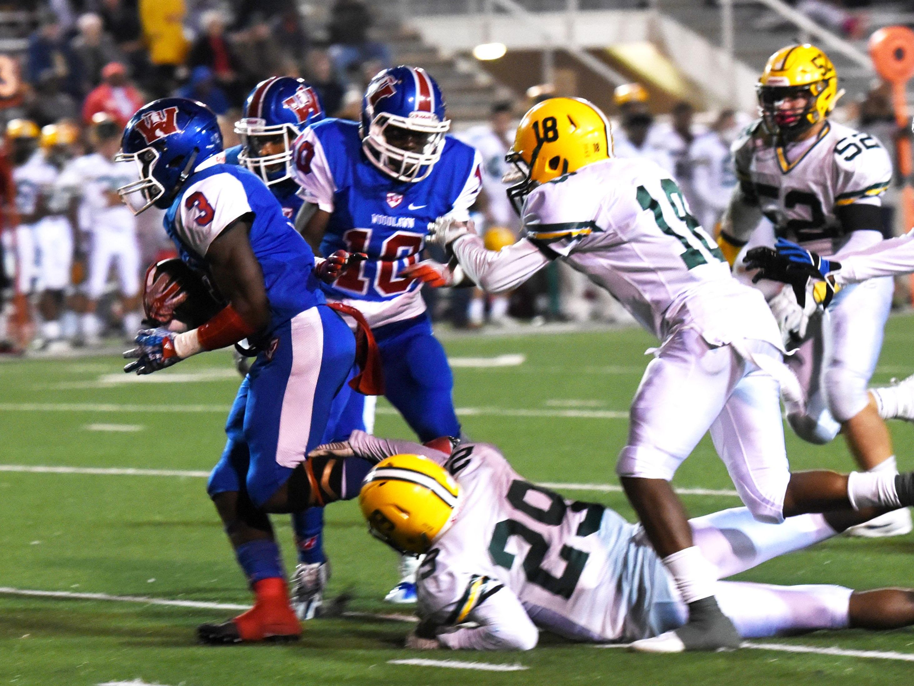 Woodlawn's Trivenskey Mosley tries to get past Cecilia's defense Friday evening at Lee Hedges Stadium.
