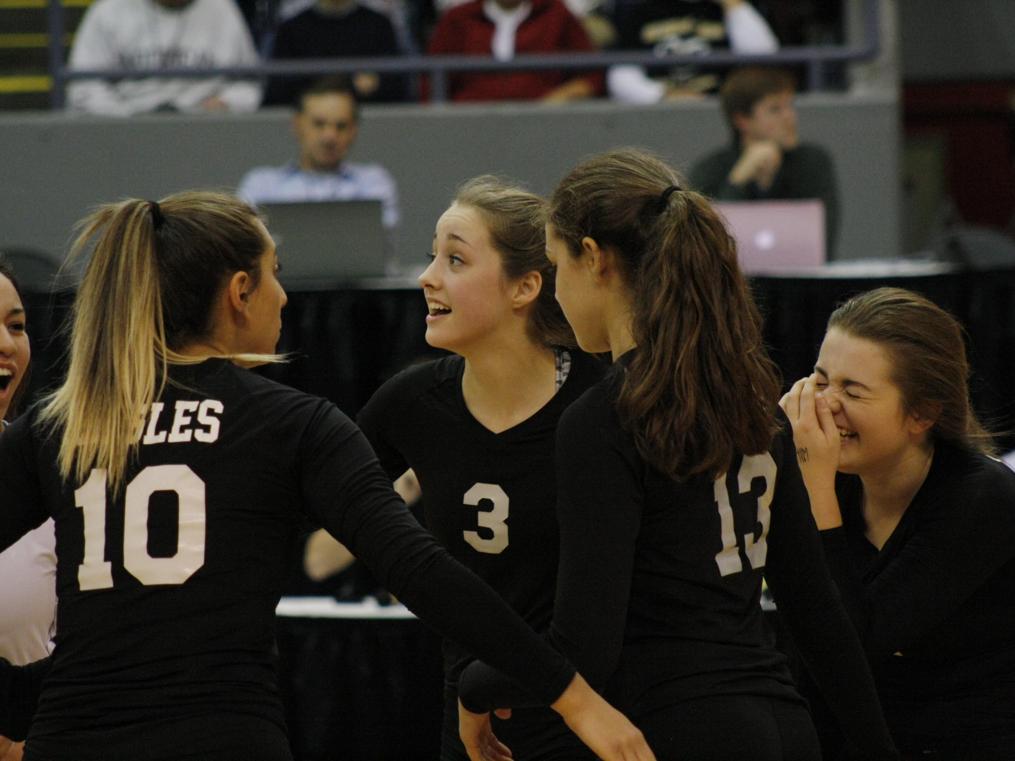 From left, Plymouth Christian's Ruth Doty, Grace Kellogg and Gabriella Kellogg celebrate a won point Friday during the third set of their semifinal win over Leland.
