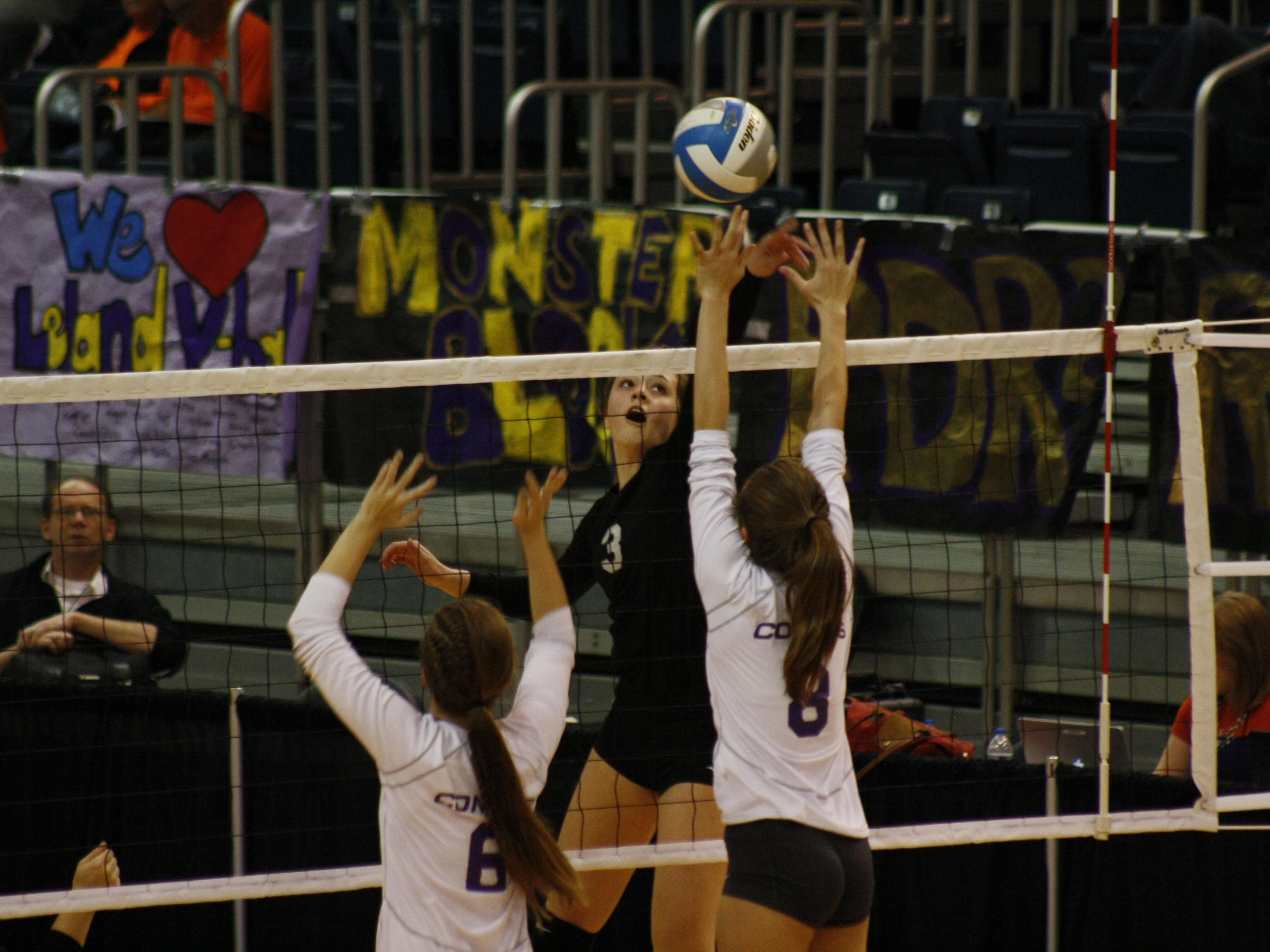 Plymouth Christian's Grace Kellogg tips the ball over the net and Leland's Hanna Elwell for a point at Kellogg Arena.