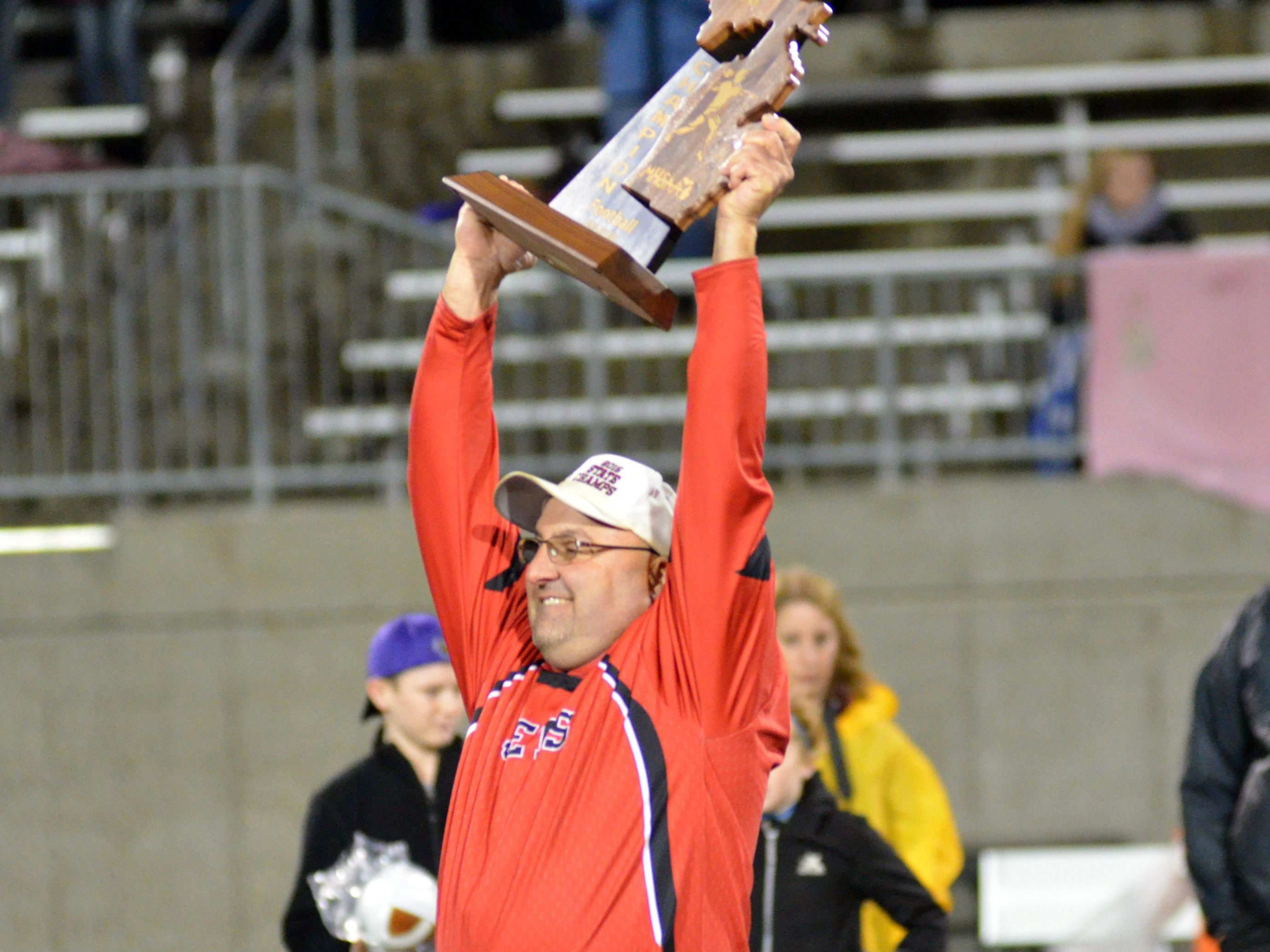 Powers North Central coach Kevin Bellefeuil holds up the 8-man state championship trophy.