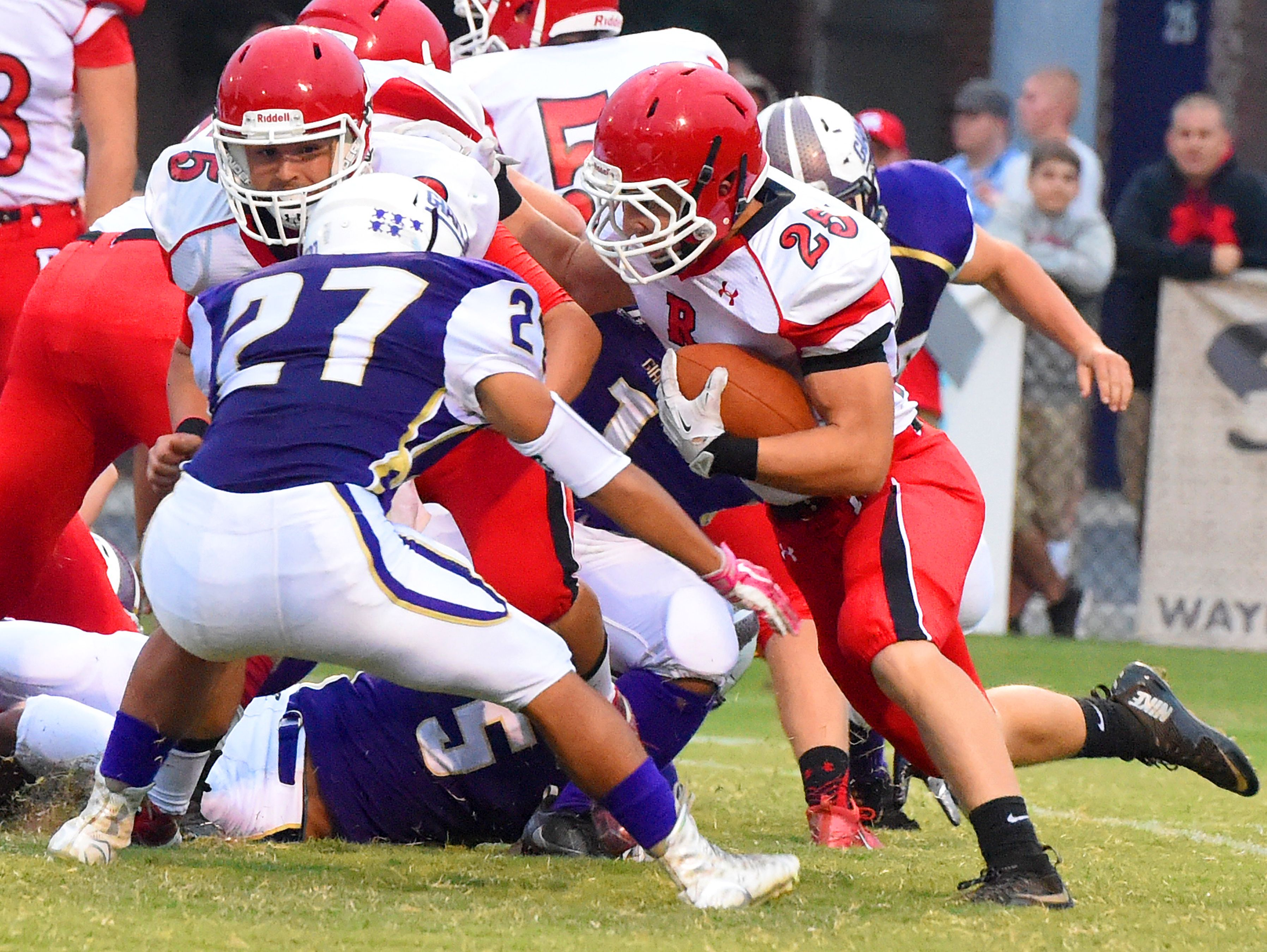 Riverheads' Brett Hostetler runs the football as teammate Chase Armstrong (left) holds off Waynesboro's Phillip Monterrozo during a football game played in Waynesboro on Friday, Sept. 16, 2016.