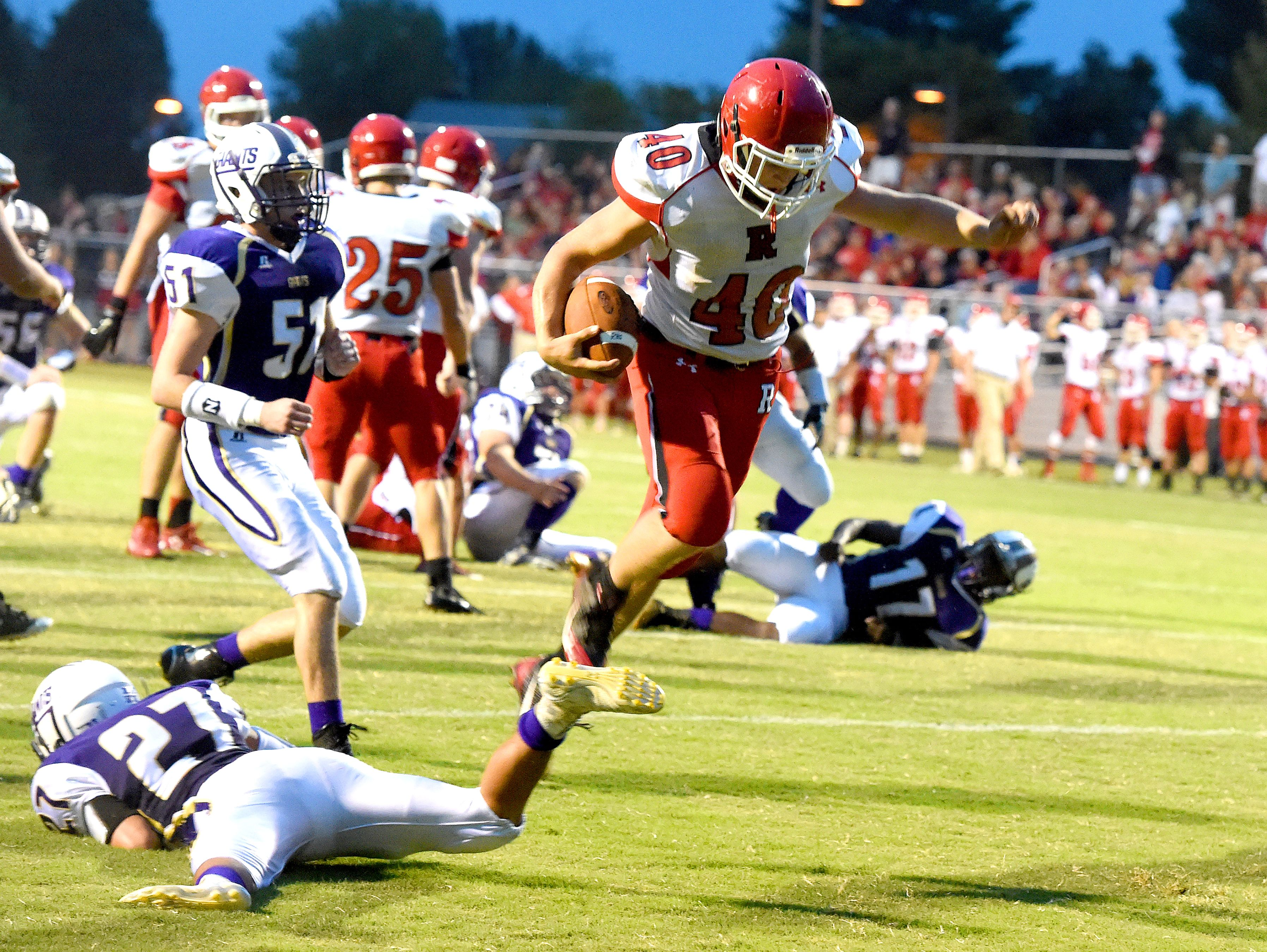 Riverheads' Harrison Schaefer jumps over Waynesboro's Phillip Monterrozo as he takes the football into the end zone for a touchdown during a football game played in Waynesboro on Friday, Sept. 16, 2016.