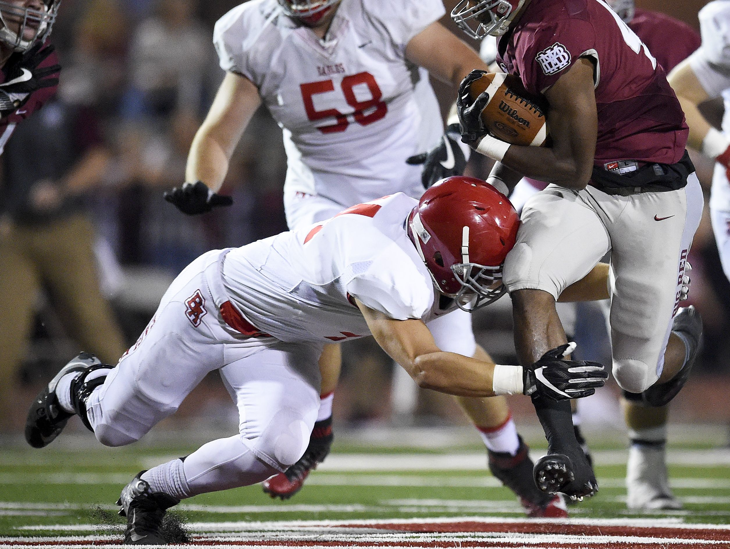 Brentwood Academy linebackerJackson Sirmon, left, tackles MBA running back Ty Chandler