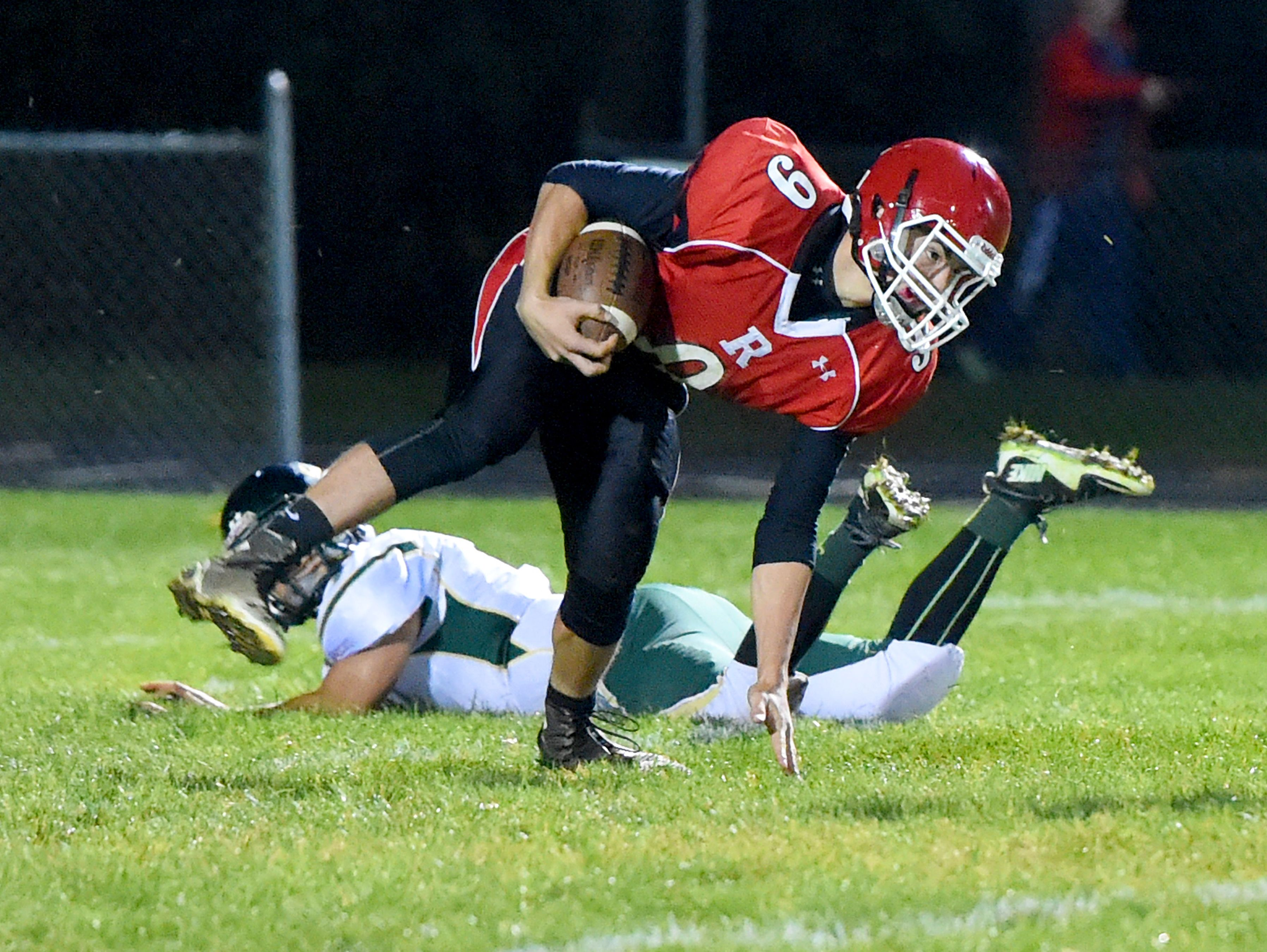 Riverheads' Tyler Smith stays on his feet with the ball after jumping over Wilson Memorial's Logan Leche to avoid the tackle during a football game played in Greenville on Friday, Oct. 21, 2016.
