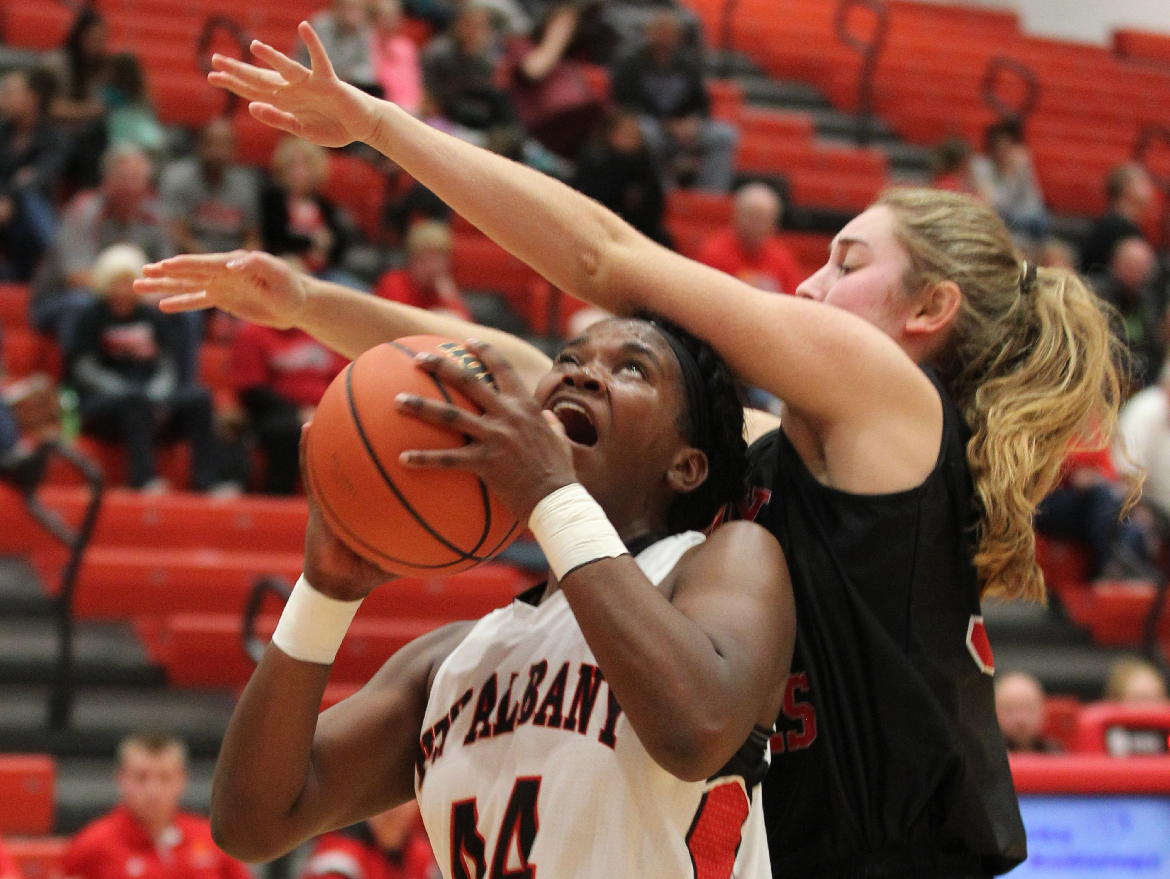 New Albany's Kelsy Taylor (44) fights to get her shot off under pressure from Brownstown Central High School's Ashley Schroer (30) during their game at New Albany High School in New Albany, Indiana. November 10, 2016