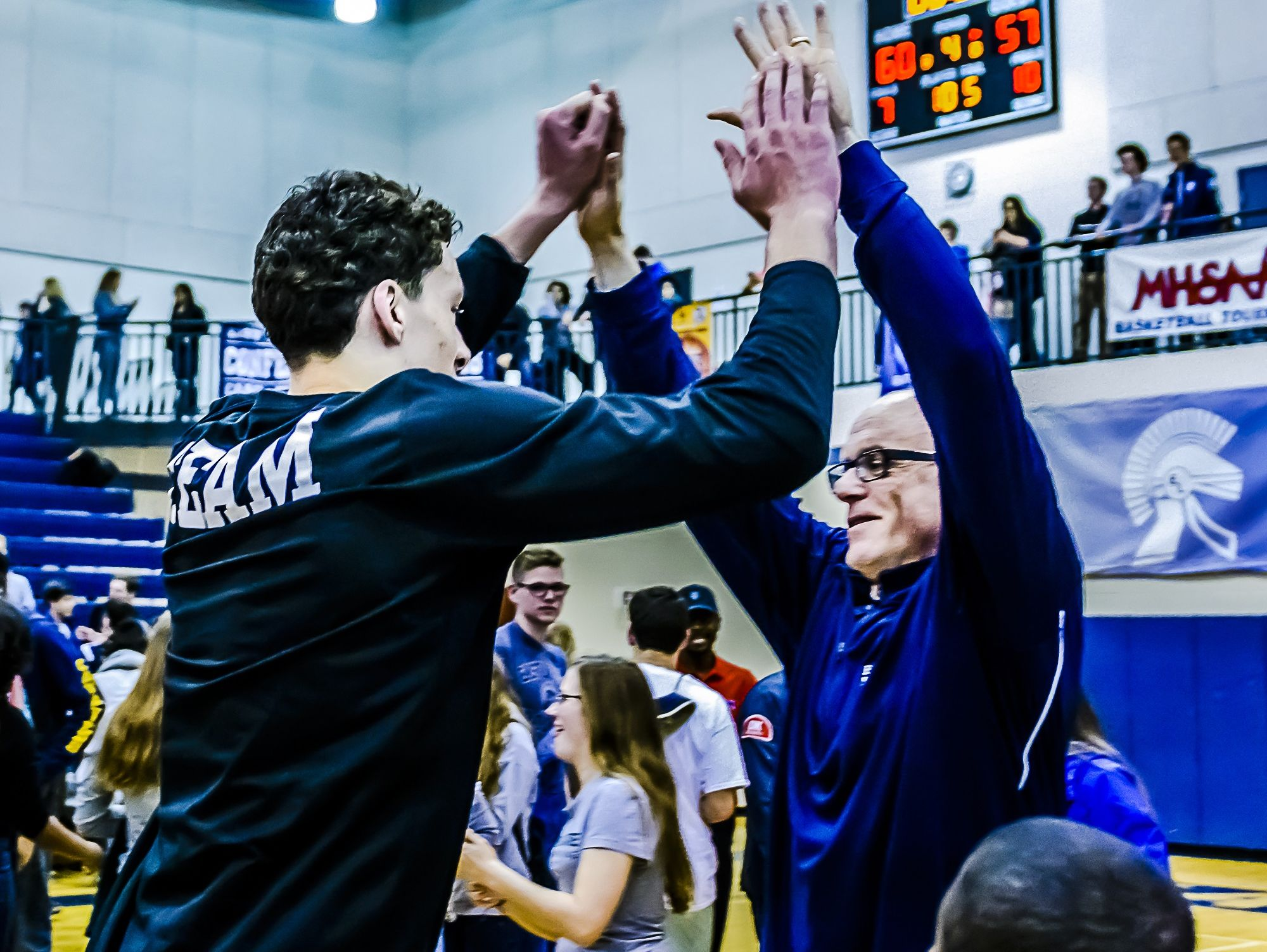 Brandon Johns, left, of East Lansing high-fives East Lansing head coach Steve Finamore last season after winning the Class A district title. Finamore, who led the Trojans to a 23-1 record in 2015, will return eight players - four starters - in the 2016 season.