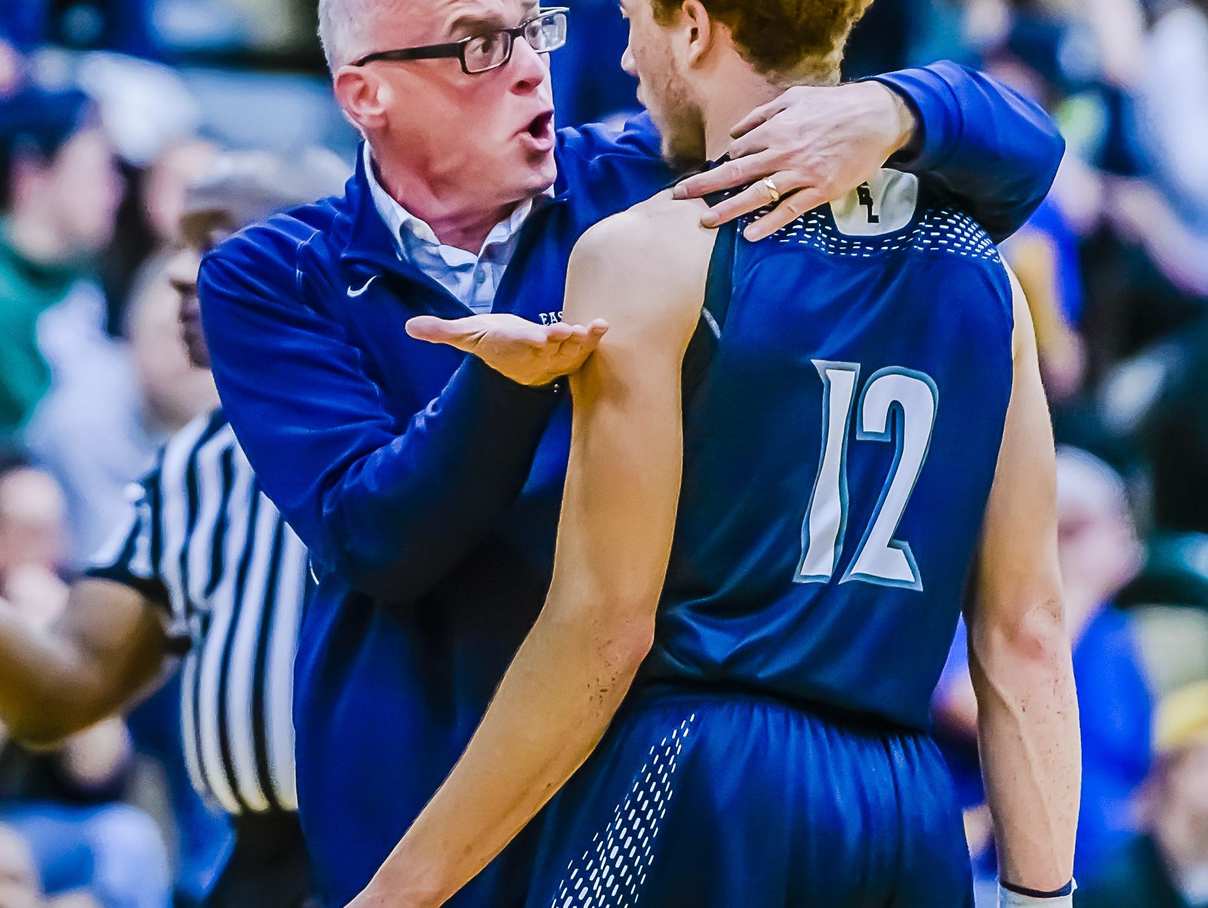 East Lansing boys basketball head coach Steve Finamore, left, speaks with DeAndre' Robinson during a game with Holt last season.