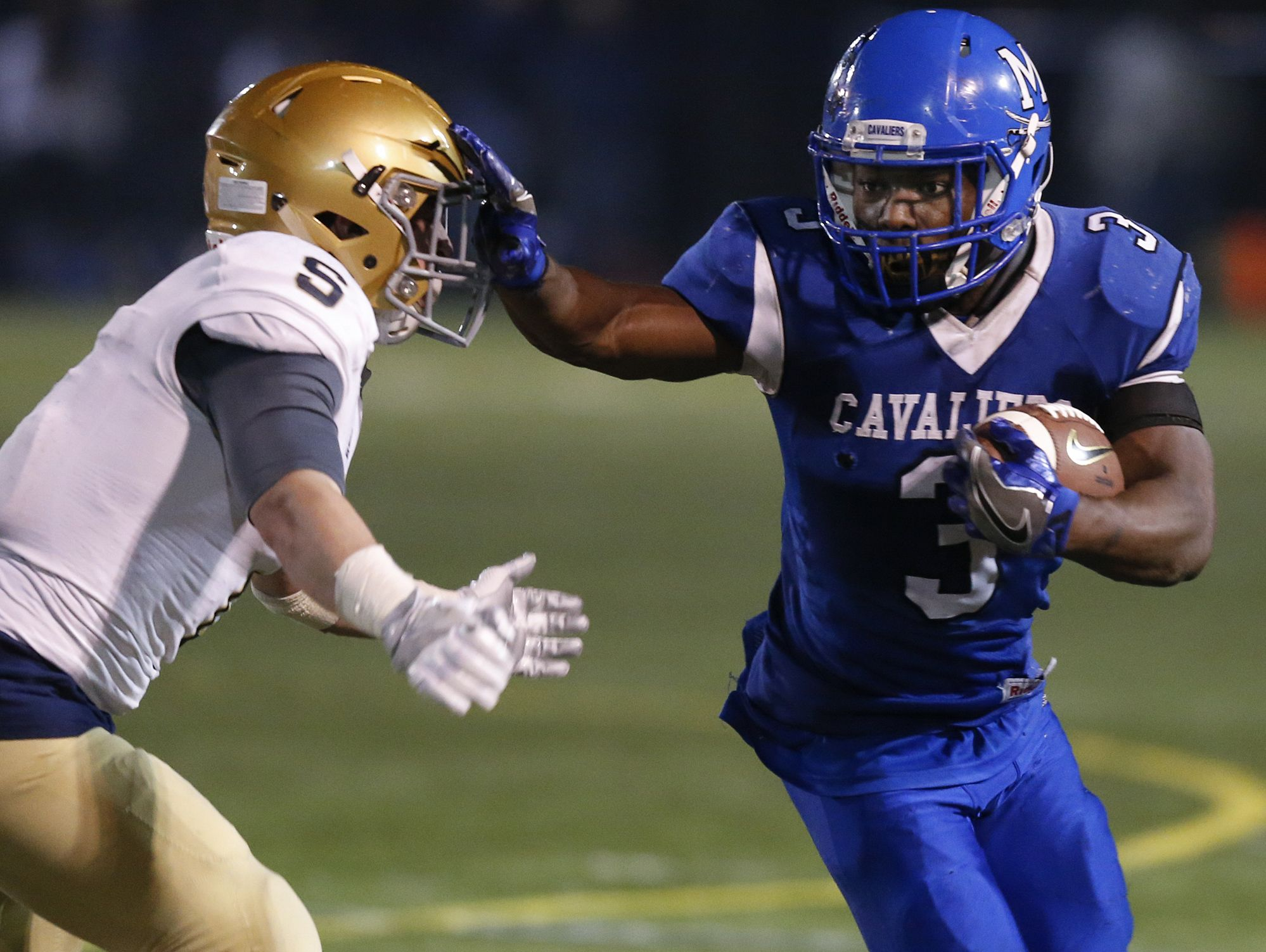 Middletown's Kedrick Whitehead (3) stiff-arms Salesianum's John Andreoli during the Cavaliers' 25-7 victory last Friday in the DIAA Division I semifinals.