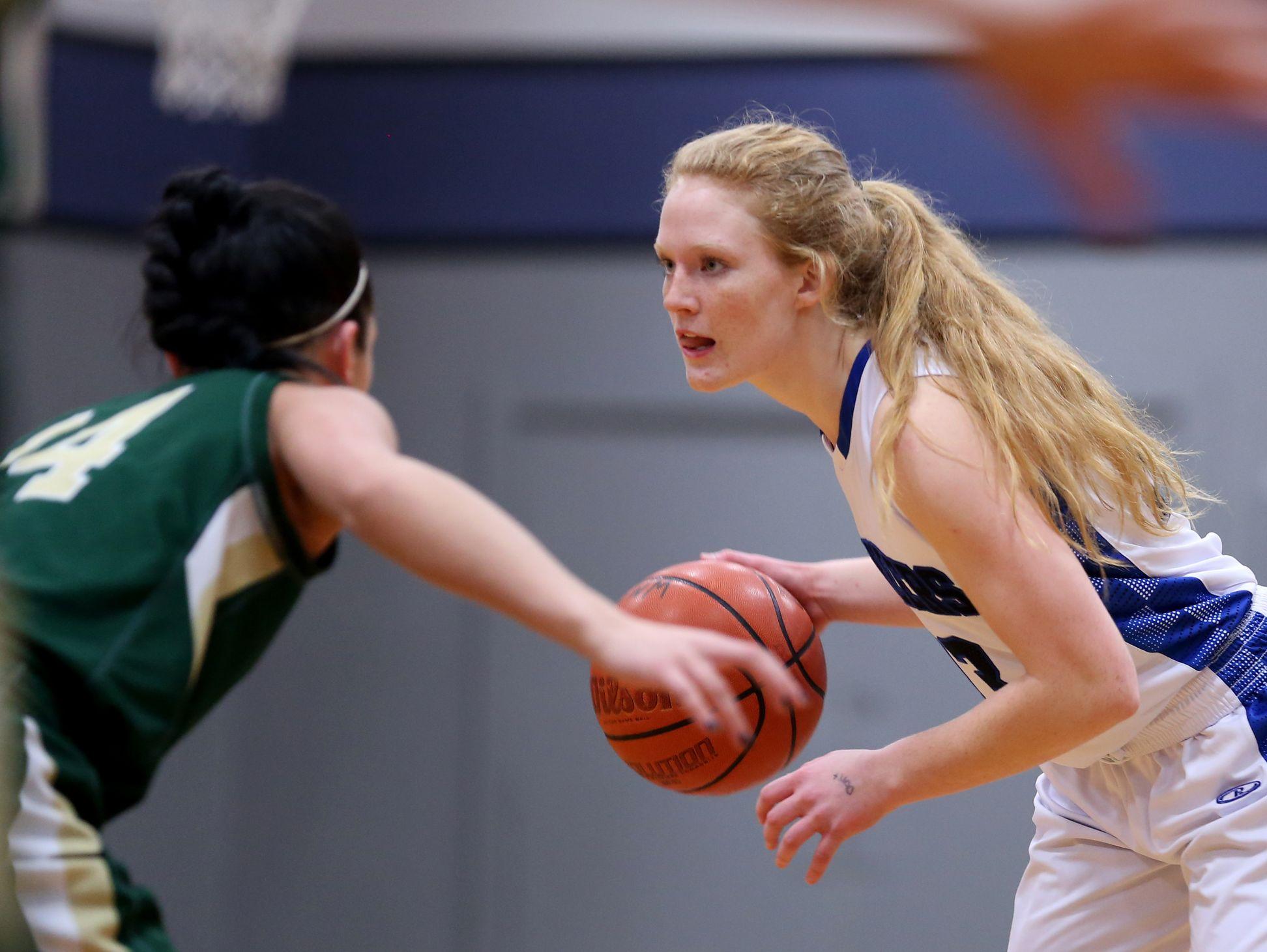Western Mennonite's Madison Hull (13) moves past Regis' Ashtyn Chamberland (14) in the Regis vs. Western Mennonite girl's basketball game at Western Mennonite High School on Wednesday, Feb. 17, 2016.