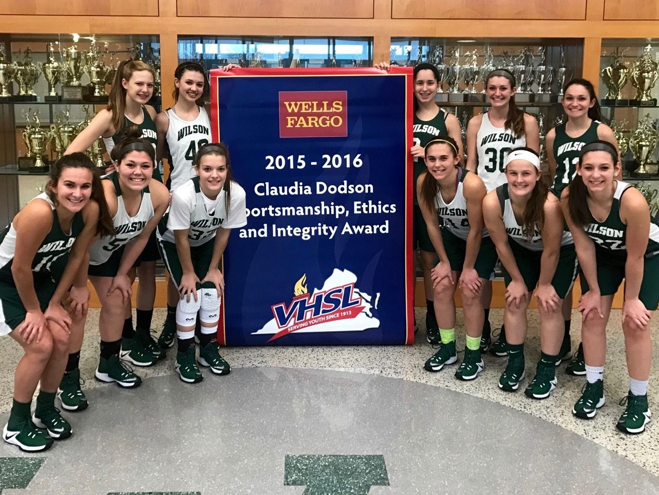 Members of Wilson Memorial's girls basketball team pose in front of the banner the school received for winning the VHSL's Claudia Dotson award for the 2015-16 school year.