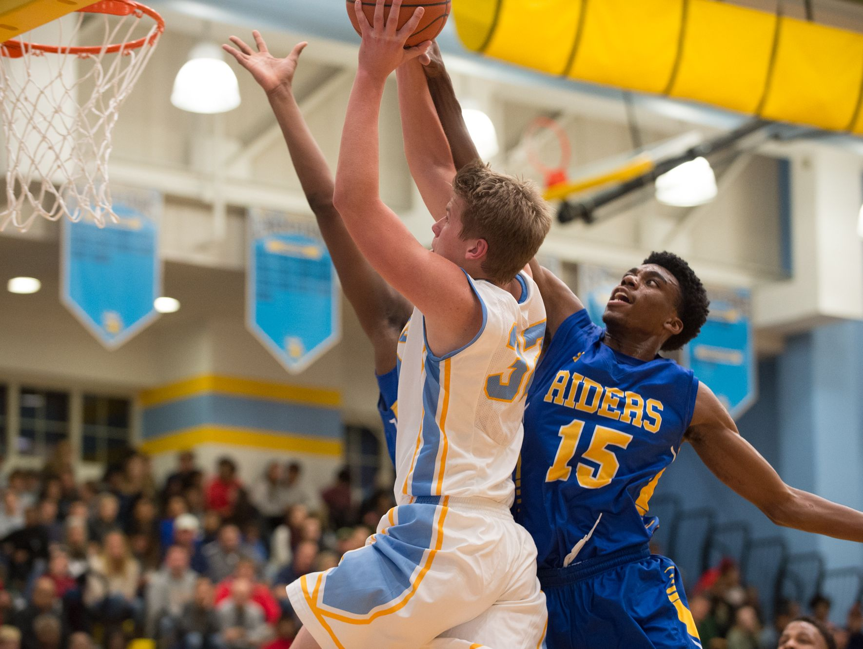 Cape Henlopen's Ian Robertson (32), left, goes up for a basket as Caesar Rodney's Shaft Clark (15) defends during their game at Cape Henlopen High School.