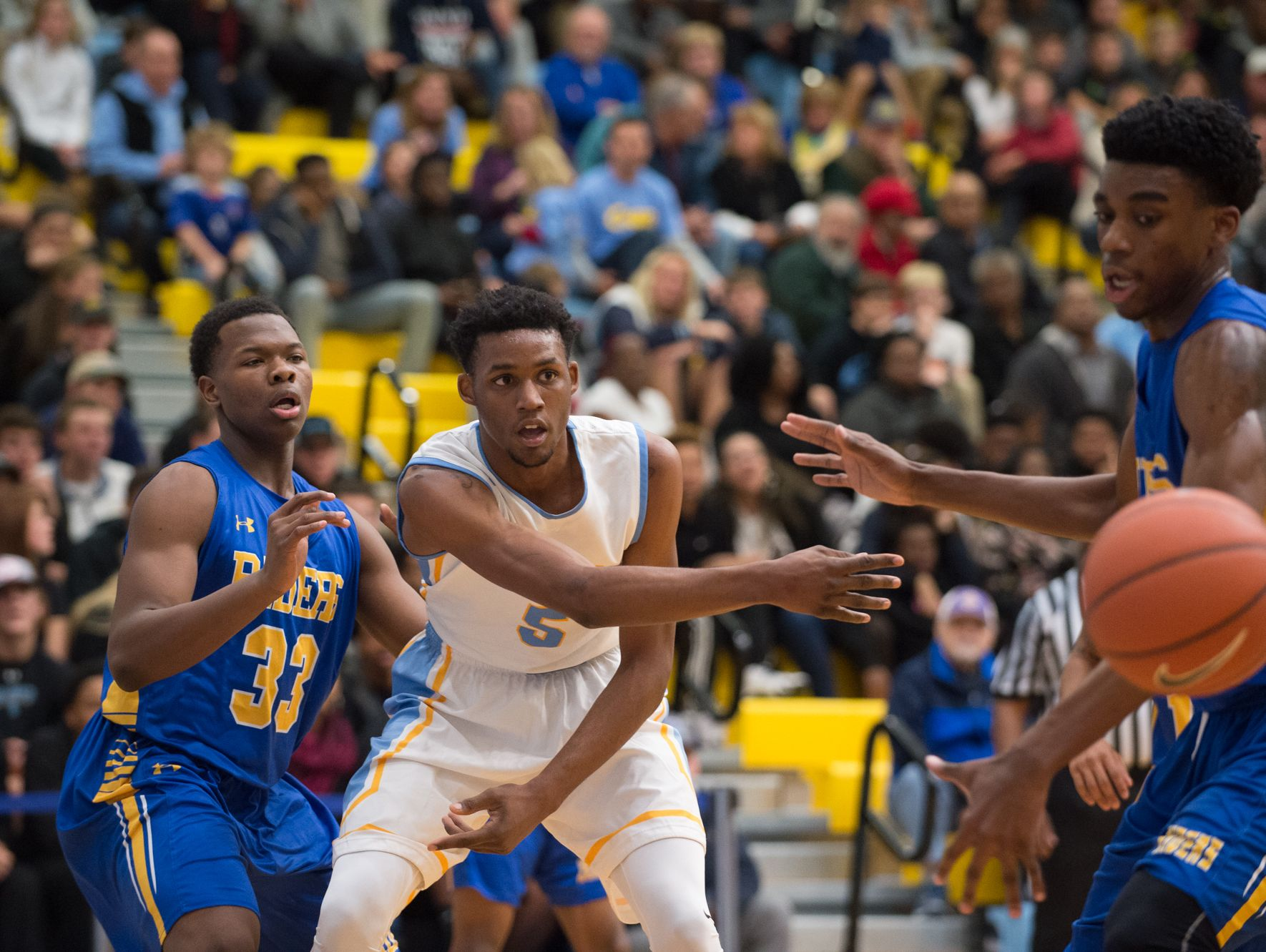Cape Henlopen's Randy Rickards (5) passes the ball in front of the hoop in their home game against Caesar Rodney.