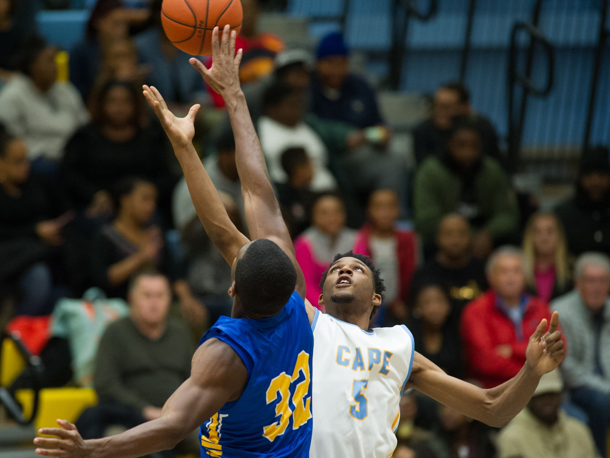 Caesar Rodney's Joseph Williams (32) and Cape Henlopen's Randy Rickards (5) jump up for the opening tip off at their game at Cape Henlopen High School.