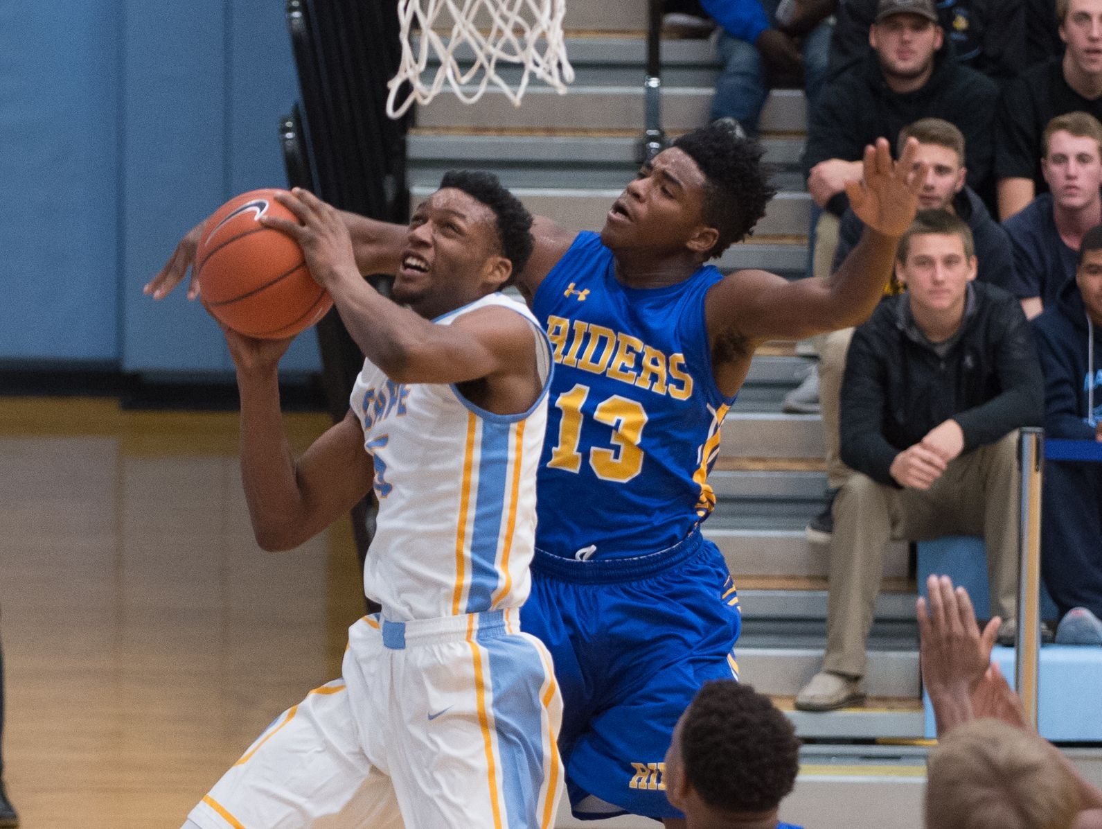 Caesar Rodney's Kairi Buie (13) reaches over the shoulder of Cape Henlopen's Randy Rickards (5) as he goes up for a basket during their game at Cape Henlopen High School.